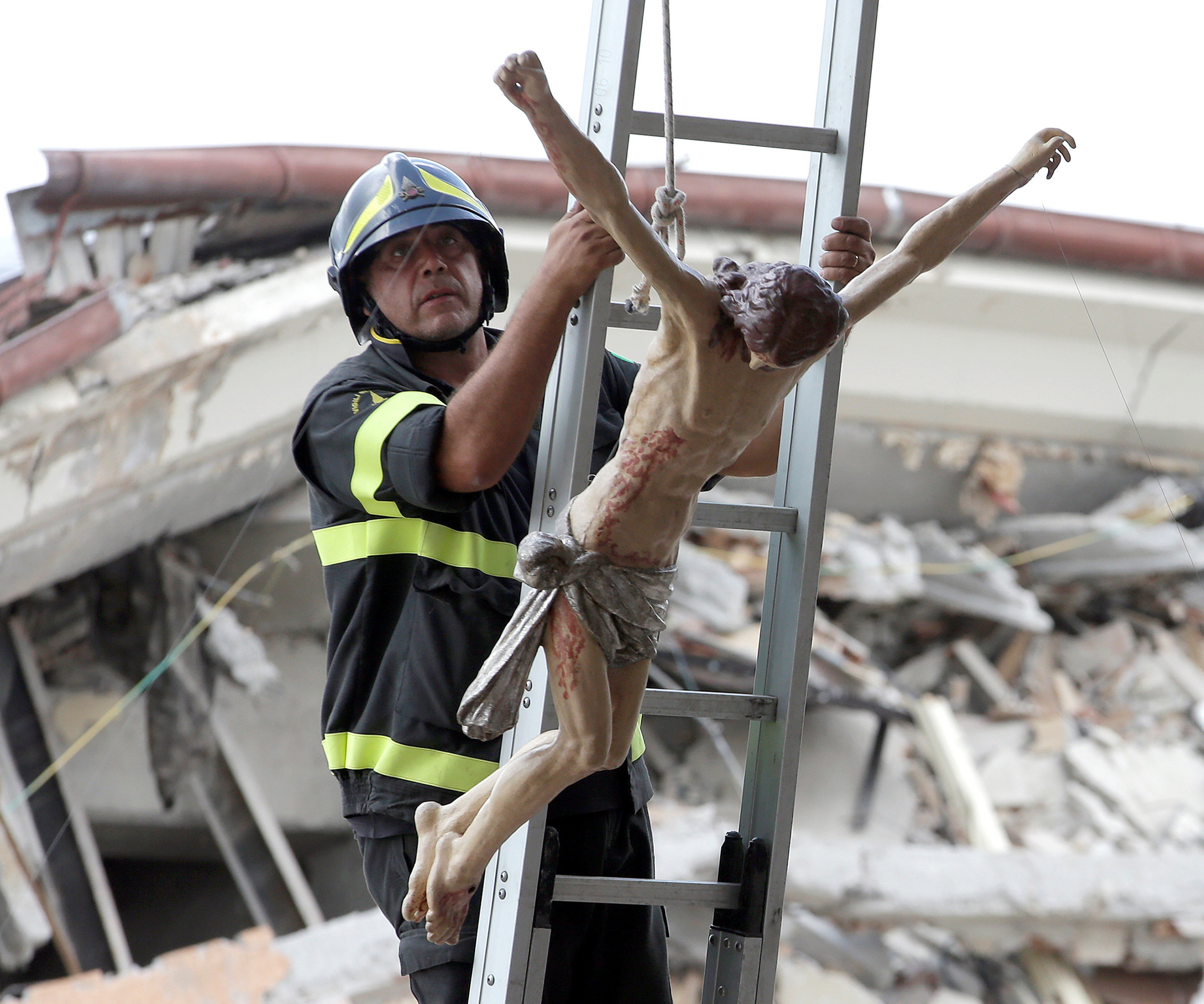 A firefighter holds a statue of Jesus rescued in the town of Amatrice following the earthquake that levelled the town in central Italy.