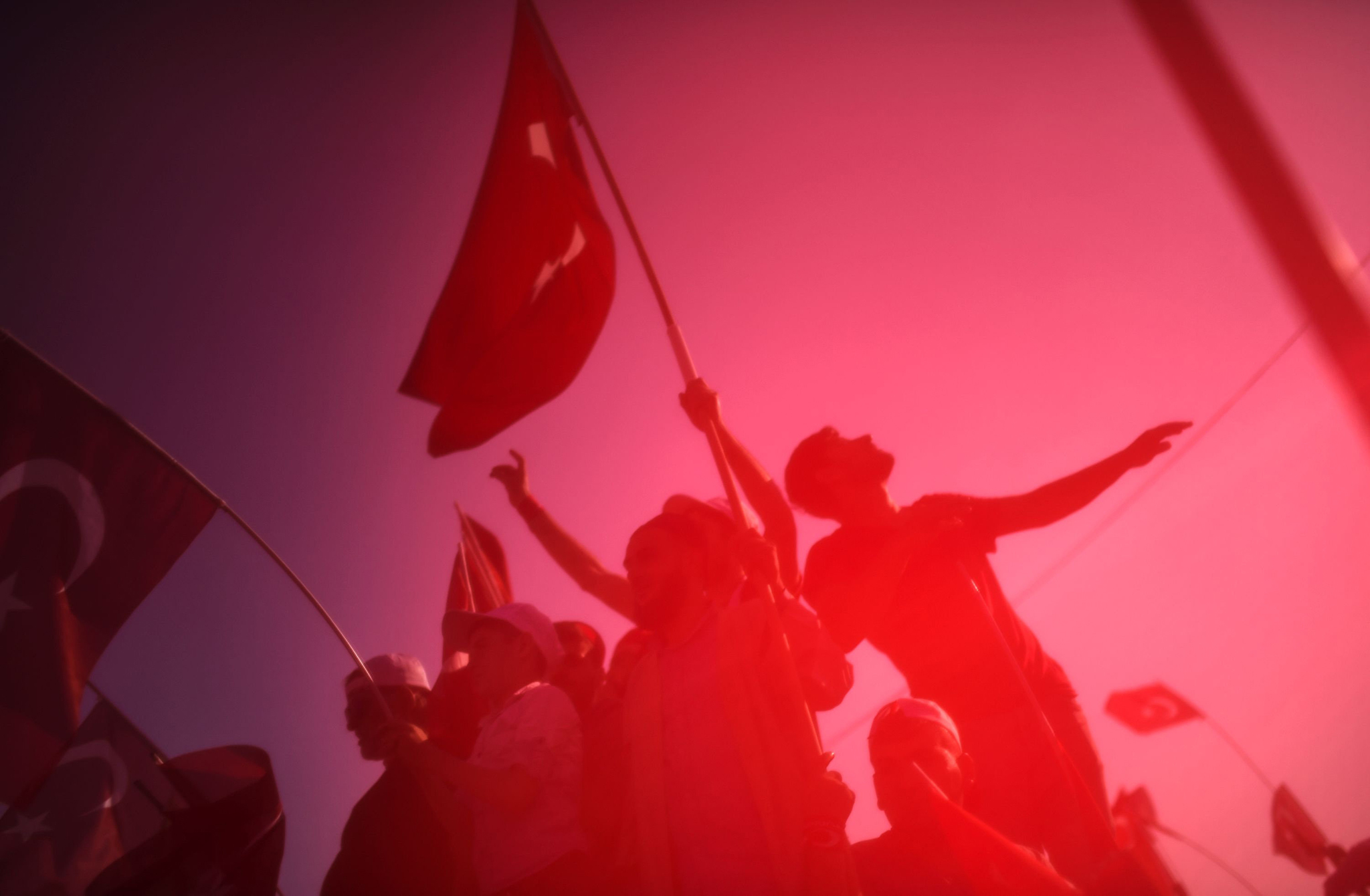 Demonstrators wave Turkish national flags as they stand in front of giant screens in Istanbul during a rally against failed military coup