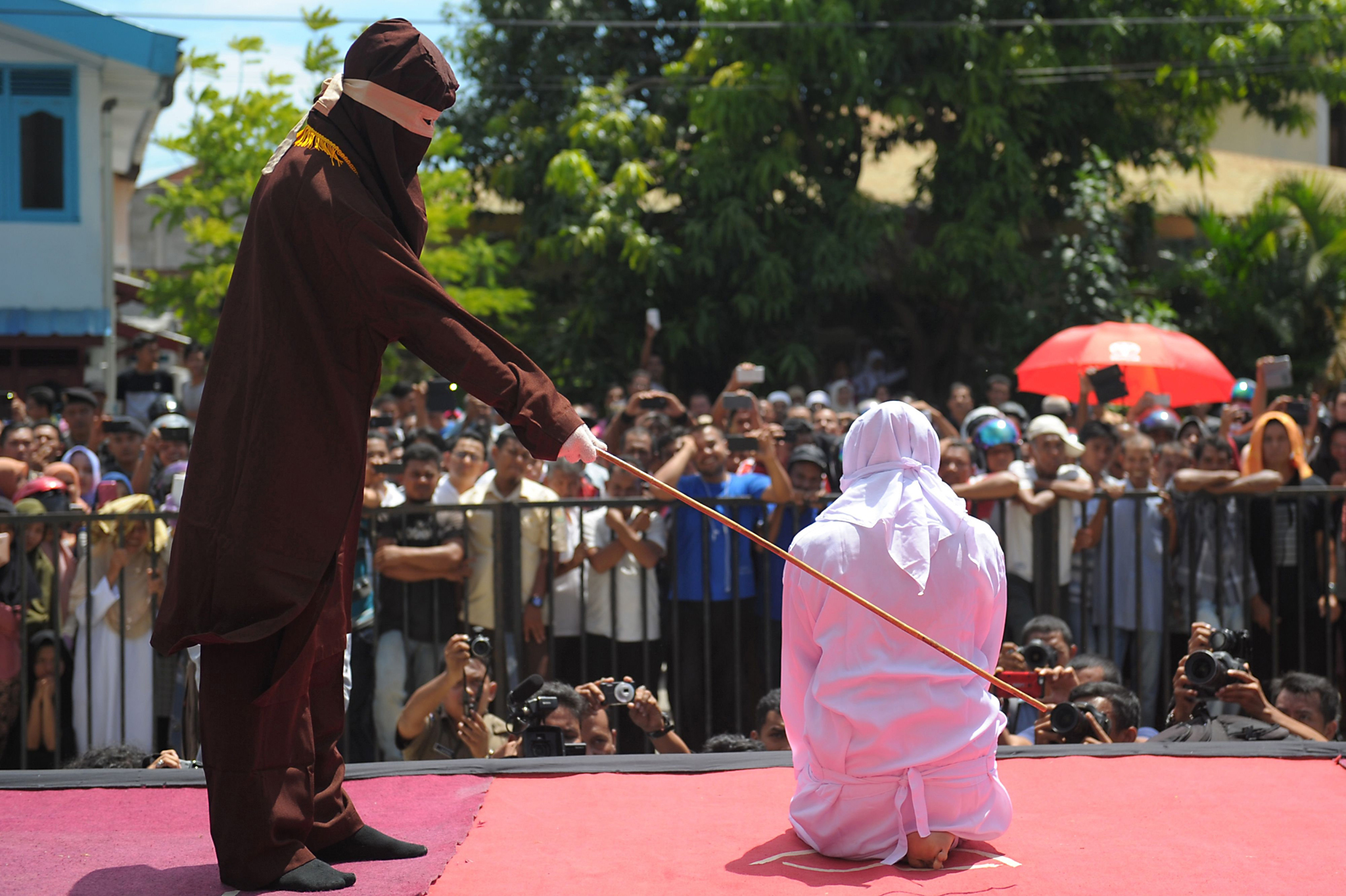 A religious officer canes an Acehnese youth onstage as punishment for dating outside of marriage, which is against sharia law, outside a mosque in Banda Aceh on August 1, 2016. The strictly Muslim province, Aceh has become increasingly conservative in recent years and is the only one in Indonesia implementing Sharia law. / AFP PHOTO / CHAIDEER MAHYUDDINCHAIDEER MAHYUDDIN/AFP/Getty Images