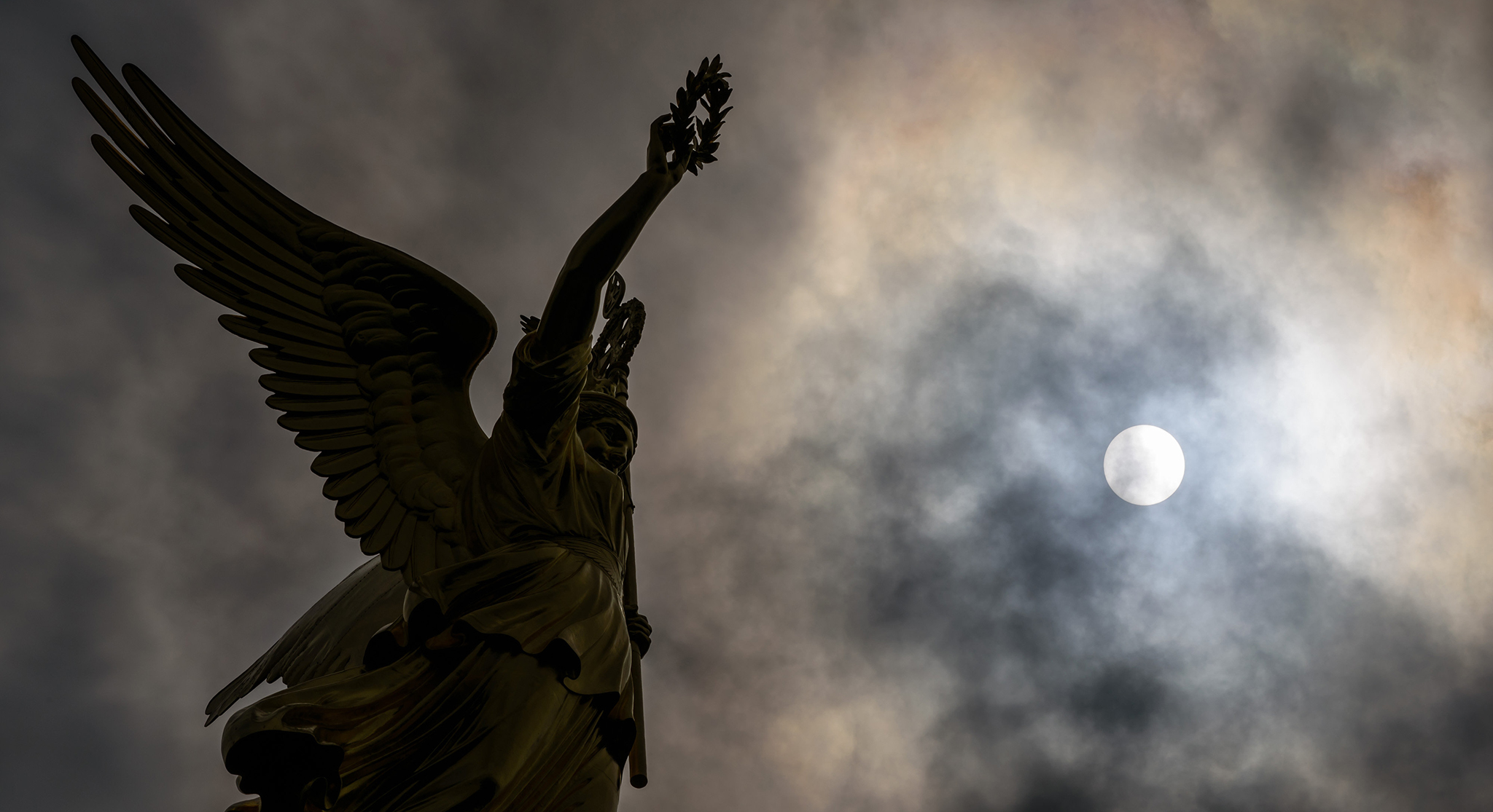 The sun is seen through the cloudy sky, beside the bronze sculpture of Victoria, in Berlin