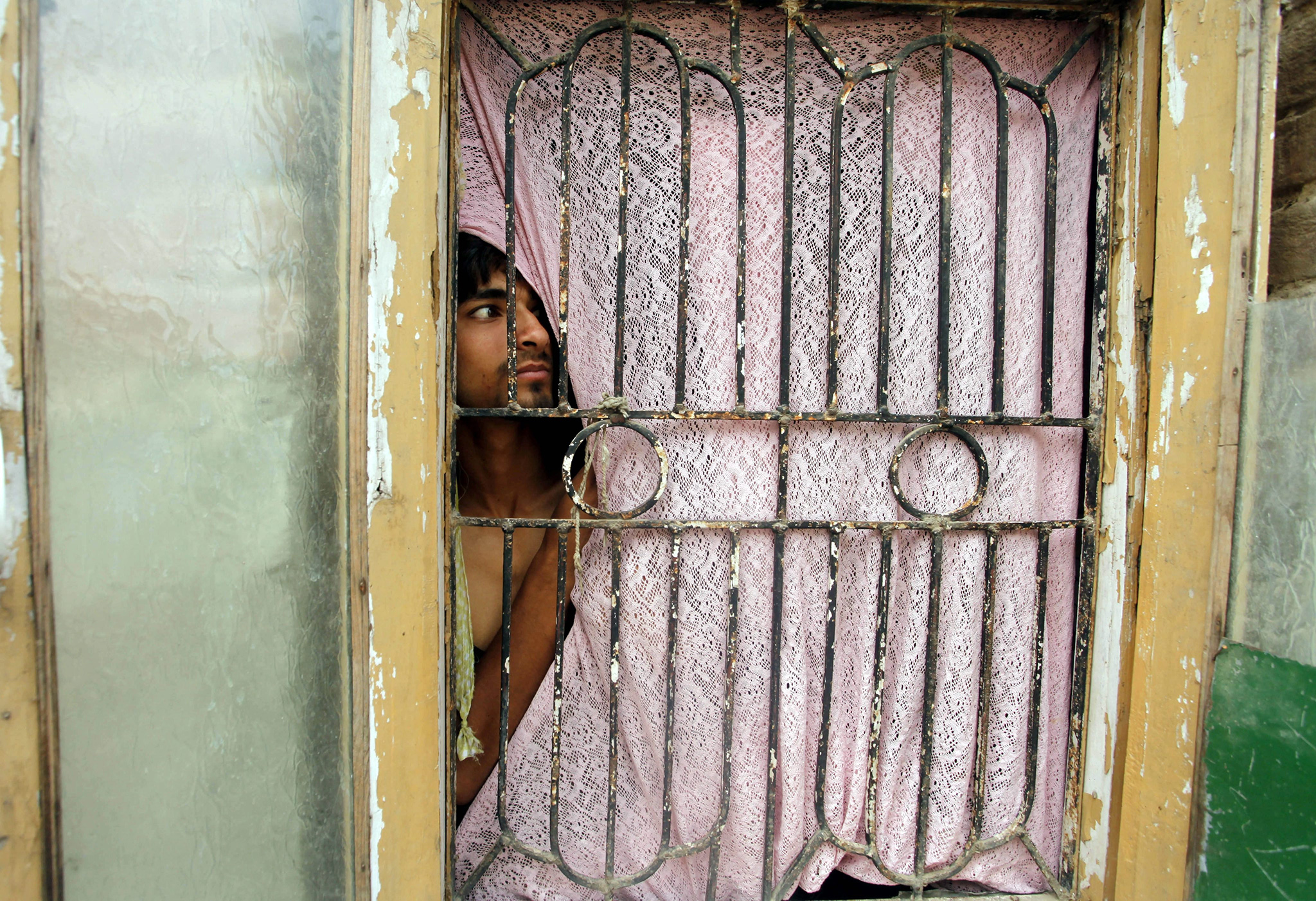 A Kashmiri boy peeps from the door of his home during a gunfight in Nowhatta area of downtown of Srinagar, the summer capital of Indian Kashmir