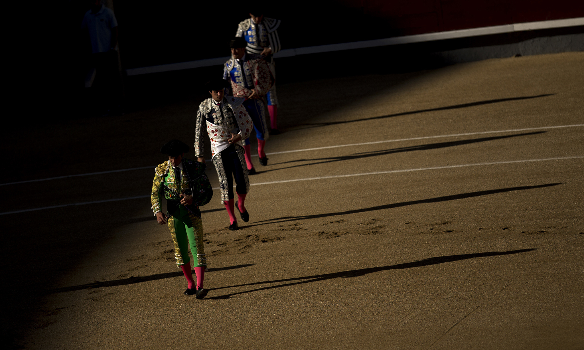 "Bullfighters and assistants walk along the ring during the ""paseillo"" or ritual entrance to the arena prior a bullfight at the Las Ventas bullring in Madrid,"