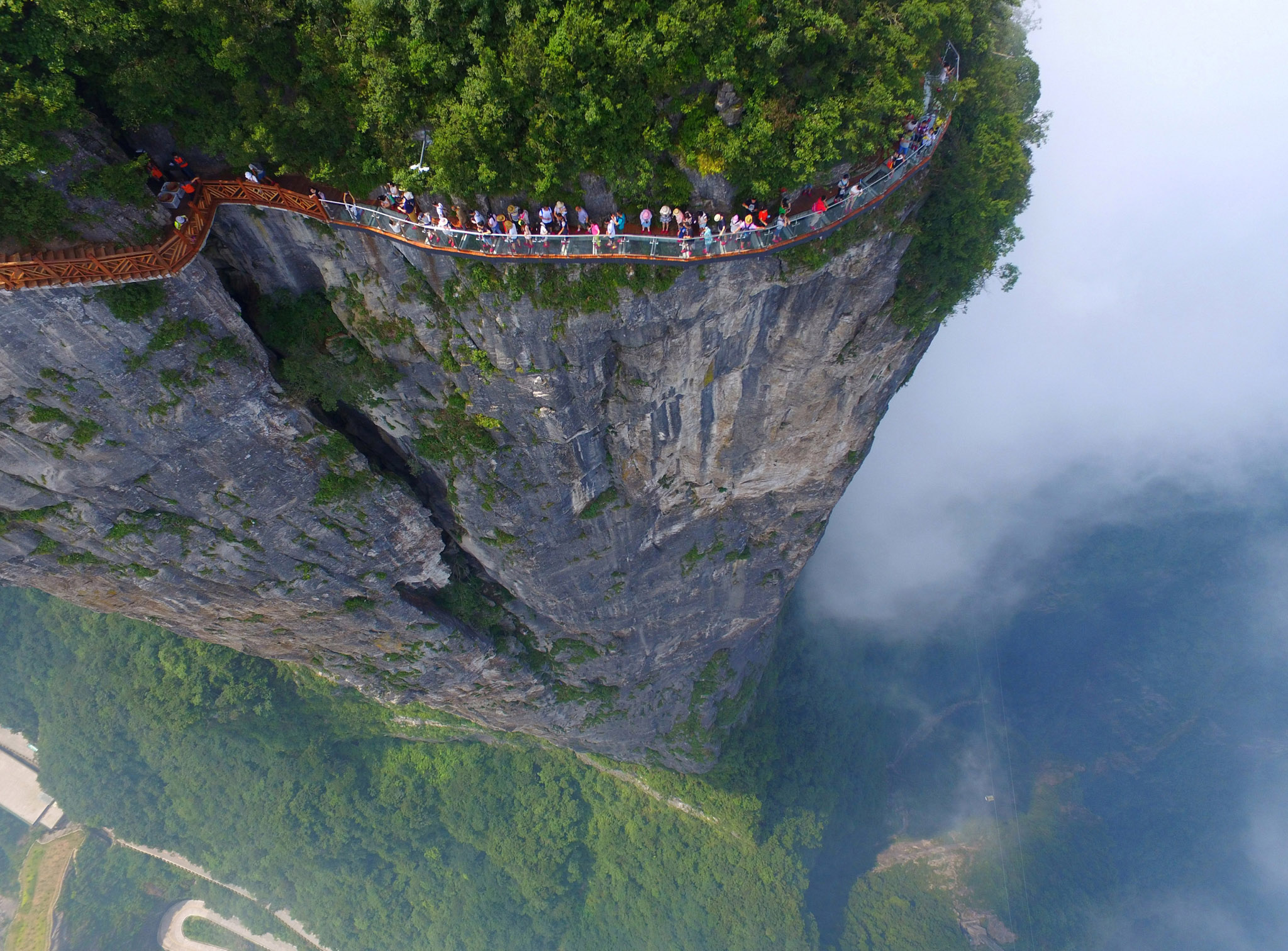 People walk on a sightseeing platform in Zhangjiajie, Hunan Province, China, August 1, 2016. REUTERS/Stringer ATTENTION EDITORS - THIS IMAGE WAS PROVIDED BY A THIRD PARTY. EDITORIAL USE ONLY. CHINA OUT. NO COMMERCIAL OR EDITORIAL SALES IN CHINA.
