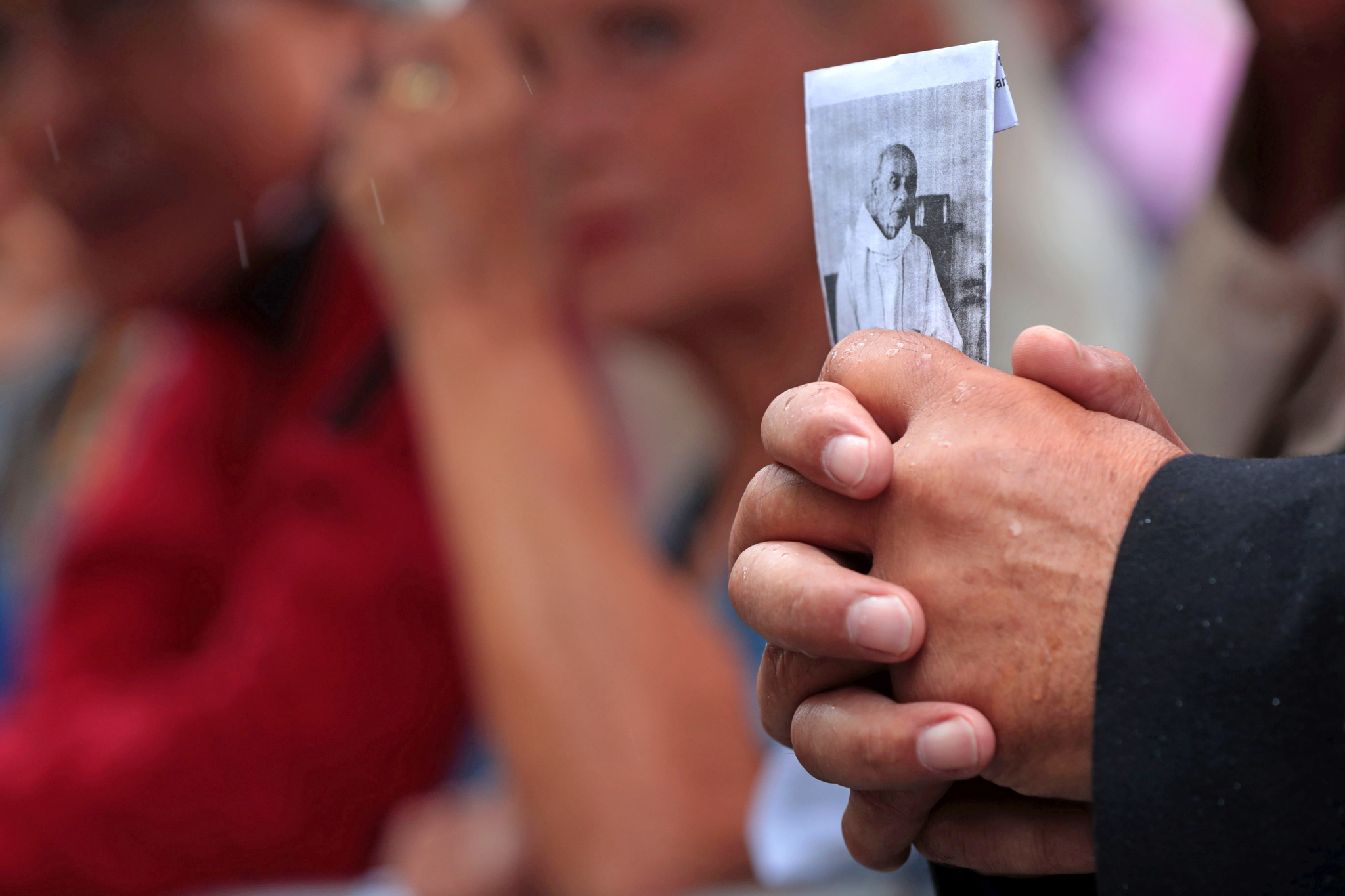 A man holds a picture of the priest Jacques Hamel outside Rouen's cathedral on August 2, 2016 during the funeral of the priest who was killed in a church in Saint-Etienne-du-Rouvray on July 26 during a hostage-taking claimed by Islamic State group.   Two jihadists, both 19, slit Hamel's throat while he was celebrating mass in an attack that shocked the country as well as the Catholic Church. The church attack came less than two weeks after another attacker ploughed a 19-tonne truck into a massive crowd celebrating Bastille Day in the Riviera city of Nice, killing 84 people and wounding more than 300 others