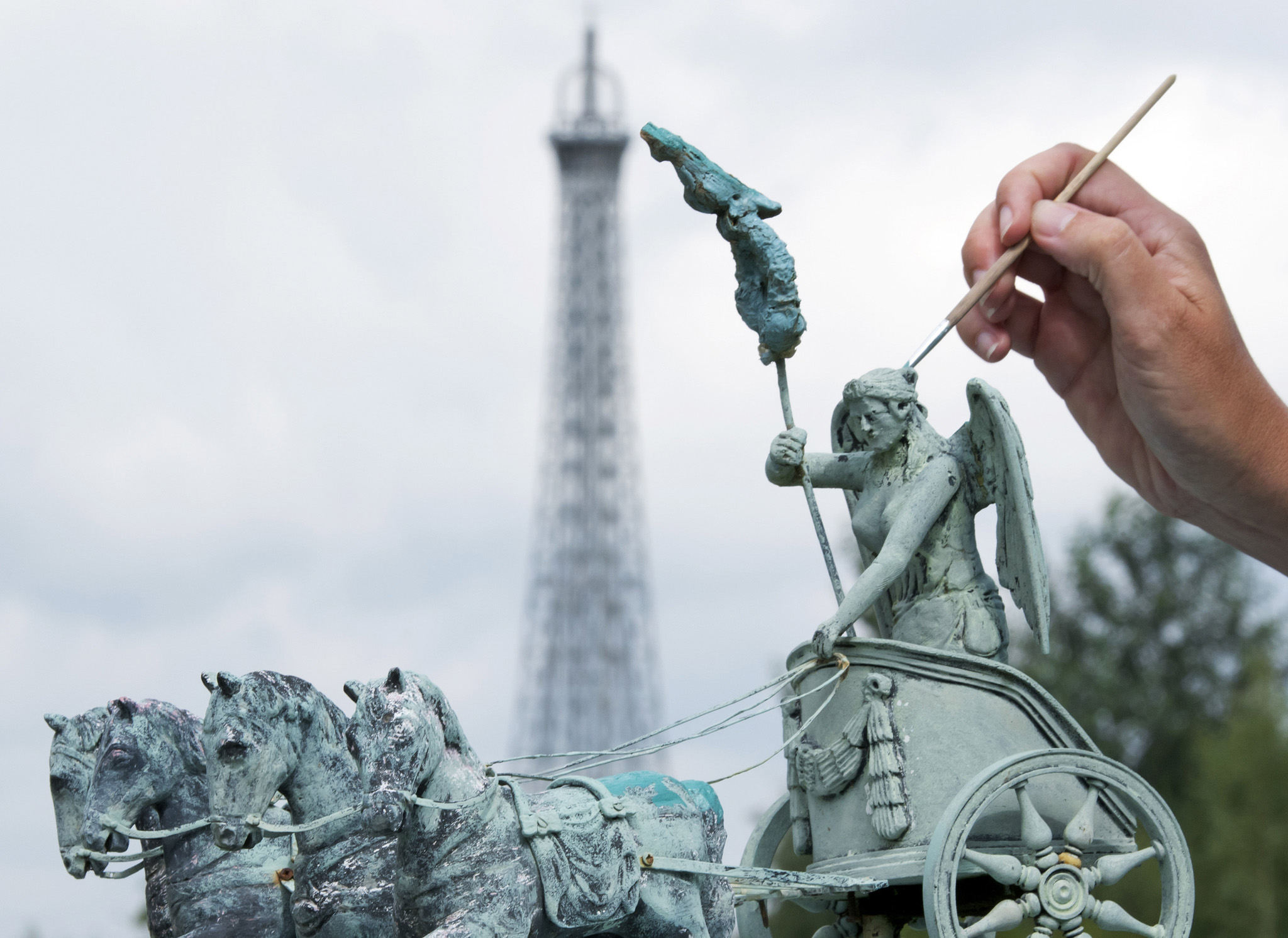 A worker paints a model of Berlin's Brandenburg Gate Quadriga in the landscape park Miniwelt (Miniworld) in Lichtenstein, eastern Germany