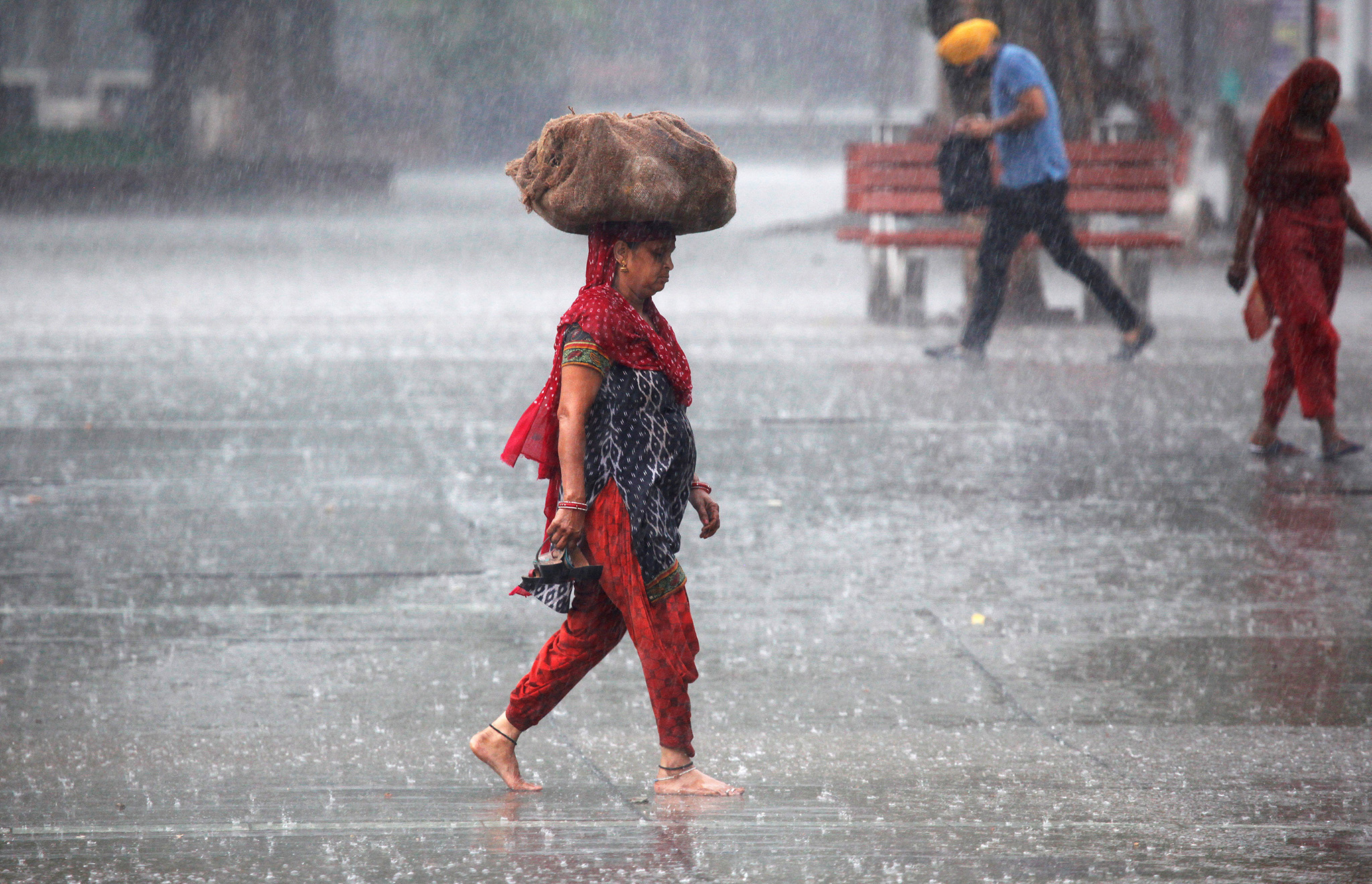 A woman carries a sack outside a market during heavy rains in Chandigarh, India,
