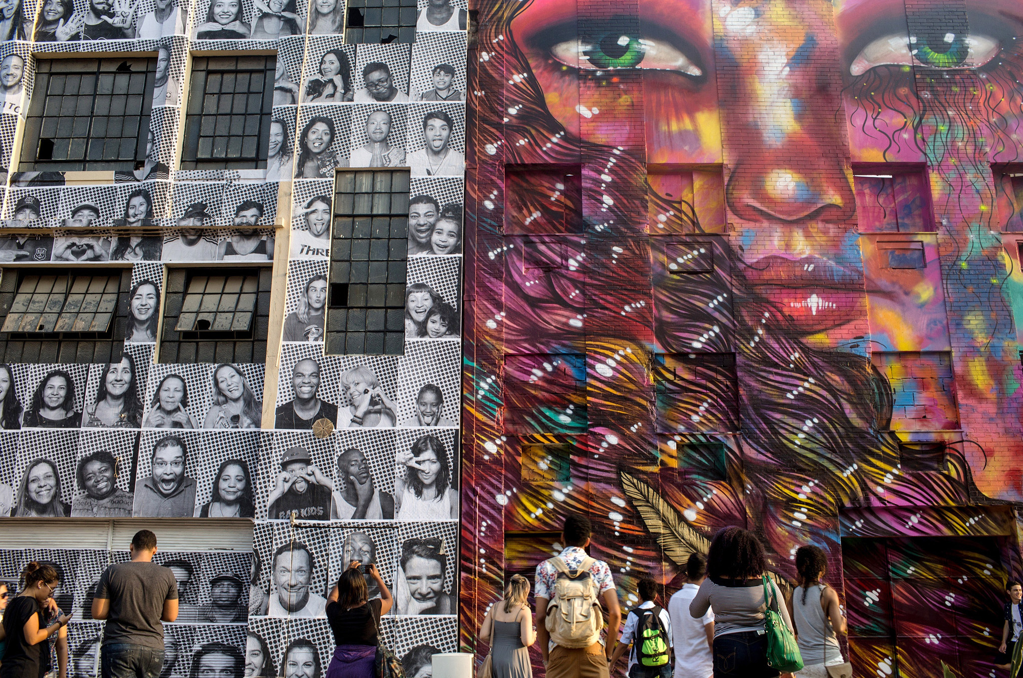 RIO DE JANEIRO, BRAZIL - AUGUST 09:  People walk in front of portraits produced by artist JR for his inside out project (L) on August 9, 2016 in Rio de Janeiro, Brazil. The artist JR has unveiled numerous art installations across Rio de Janiero celebrateing olympic athletes.  (Photo by Chris McGrath/Getty Images)