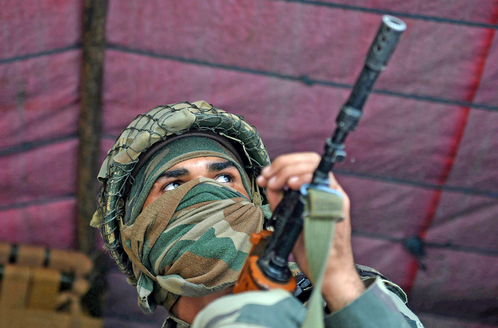 An Indian Border Security Force (BSF) soldier sits inside a truck upon arrival with others in Srinagar on August 23, 2016, to join thousands of federal forces and local policemen already deployed in the Kashmiri capital to contain a 46-day-old unrest.  Official sources said that some 2,600 additional paramilitary troopers are being flown into Srinagar from Gujarat, Rajasthan and West Bengal to supplement the governments effort to contain the situation in the restive state of Jammu and Kashmir.