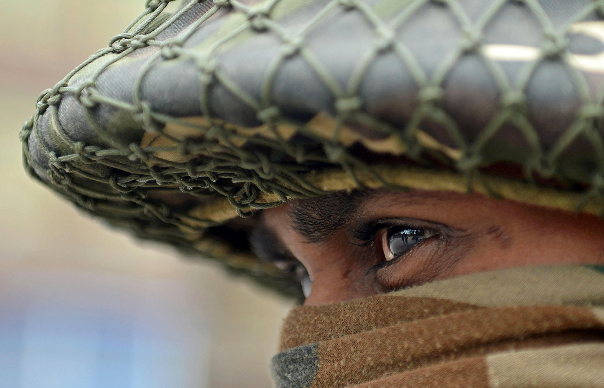 An Indian paramilitary trooper stands guard during a curfew in the Batmaloo area of Srinagar
