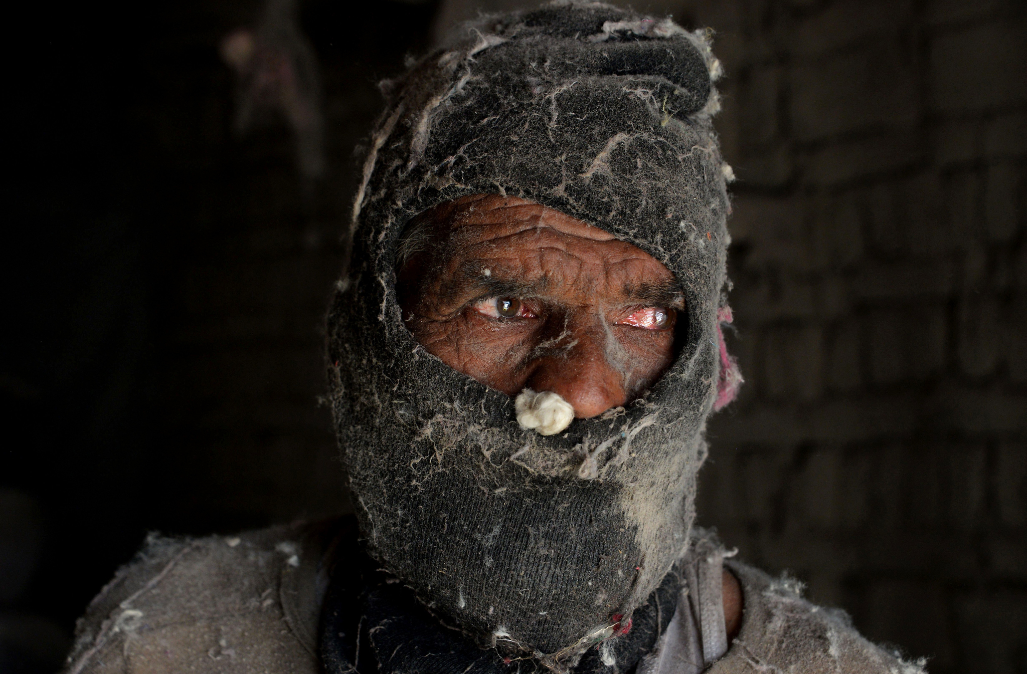 TOPSHOT - An Afghan labourer looks on as he works at a traditional cotton factory in Jalalabad on July 31, 2016. / AFP