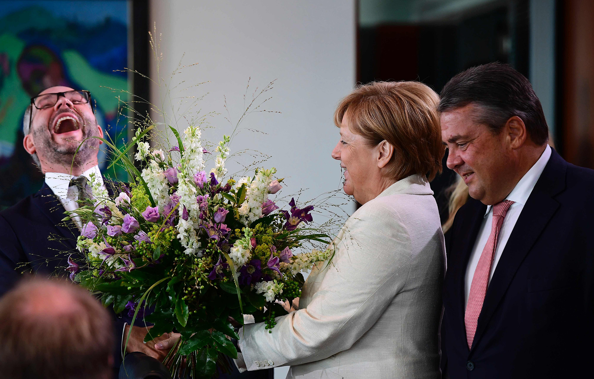 German Chancellor Angela Merkel and German Vice Chancellor, Economy and Energy Minister Sigmar Gabriel (R) hand over birthday flowers to State Minister at the Foreign Ministry Michael Roth (L) before the weekly cabinet meeting in Berlin on August 24, 2016. / AFP PHOTO / TOBIAS SCHWARZTOBIAS SCHWARZ/AFP/Getty Images