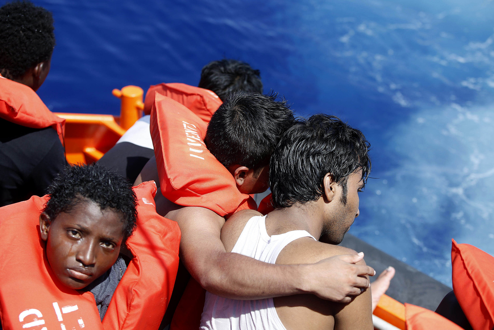 In this photo released by Italian Red Cross Friday Aug. 19, 2016 migrants embrace each other during a rescue operation at the Mediterranean sea, Thursday, Aug. 18, 2016. At least five people have died on Thursday morning during the sinking of a wooden boat full with migrants as they tried to reach the Italian coasts.