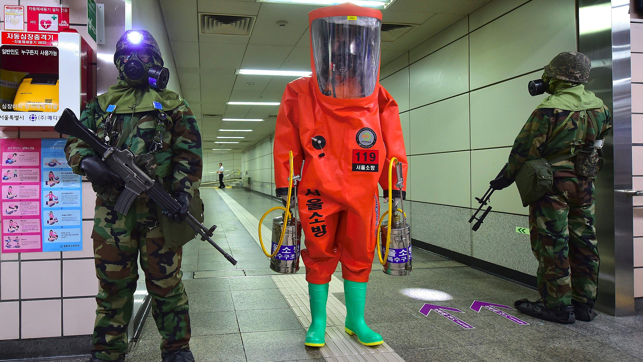 A rescue member (C) in full protective gear stands amongst South Korean soldiers wearing gas masks during an anti-terror drill on the sidelines of South Korea-US joint military exercise, called Ulchi Freedom, at a subway station in Seoul on August 23, 2016. South Korea and the United States kicked off large-scale military exercises on August 22, triggering condemnation and threats of a pre-emptive nuclear strike from North Korea