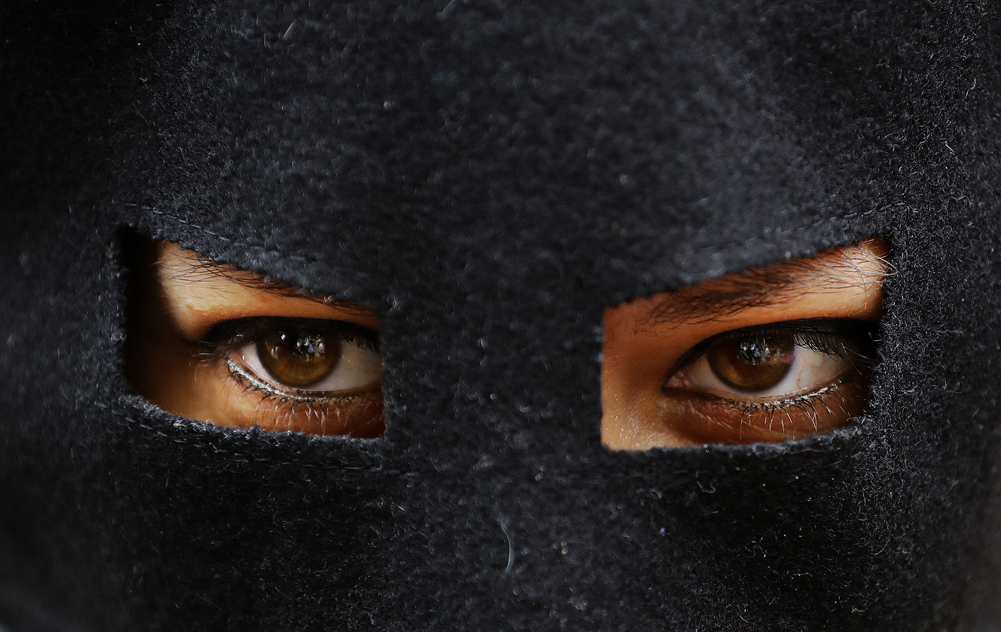 "An activist protests wears a mask outside the French embassy during, the ""wear what you want beach party"" in London, Thursday, Aug. 25, 2016. The protest is against the French authorities clampdown on Muslim women wearing burkinis on the beach. (AP Photo/Frank Augstein)"