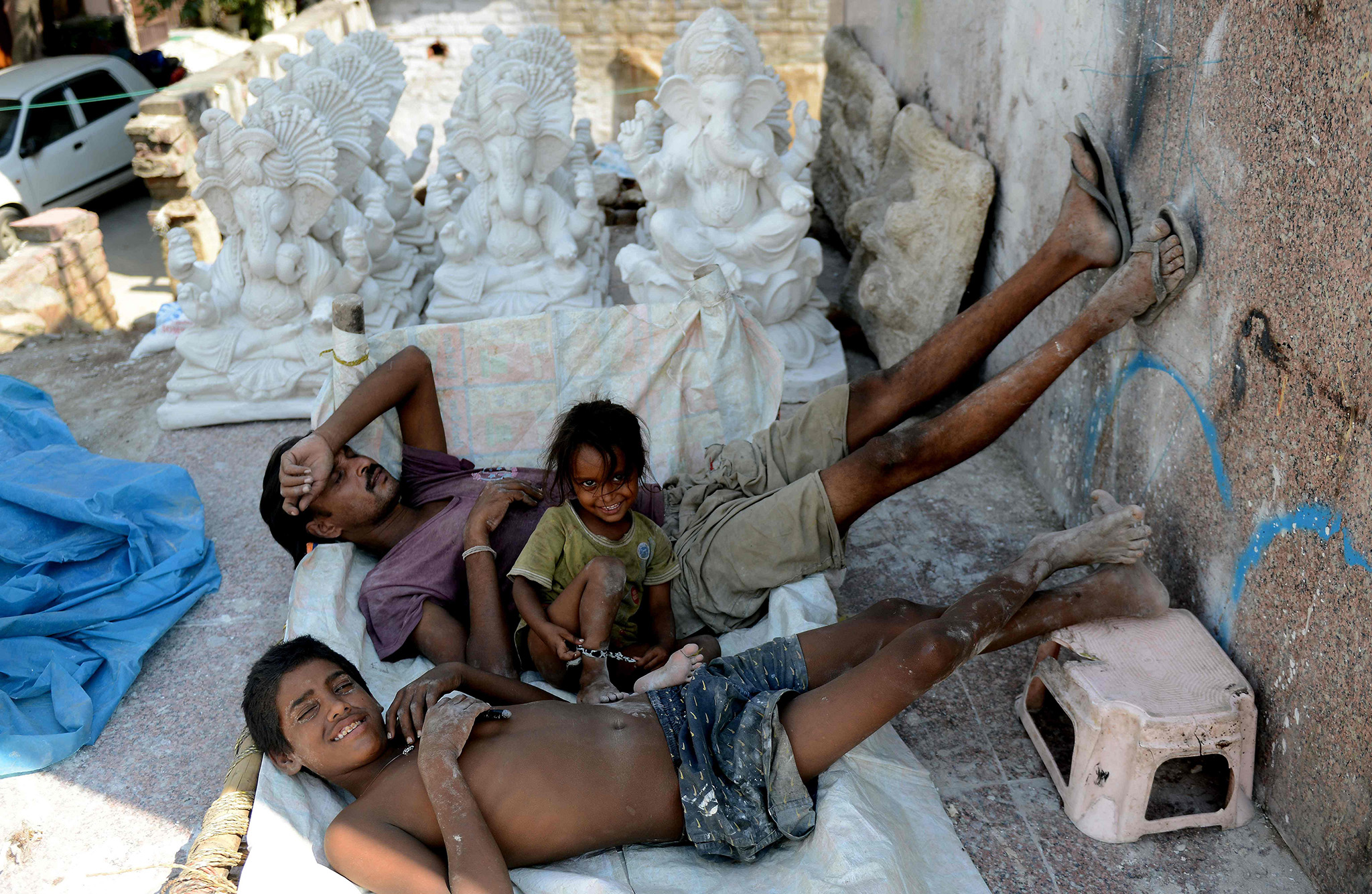 Indian workers take a nap near idols of the elephant-headed Hindu god Lord Ganesha at a roadside workshop in New Delhi on August 8, 2016.