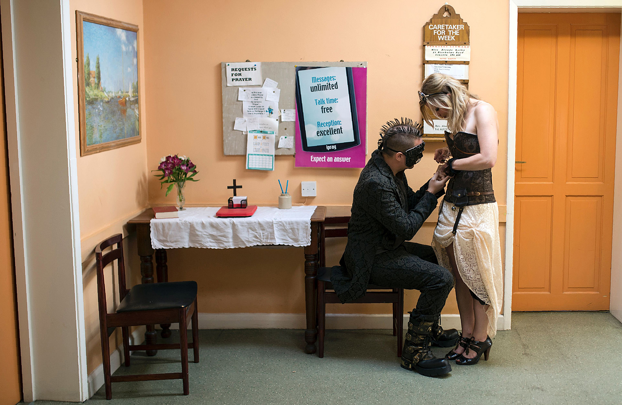 Steampunk enthusiasts fix their attire in a church hall on the first day of 'The Asylum Steampunk Festival' in Lincoln, northern England on August 26, 2016.