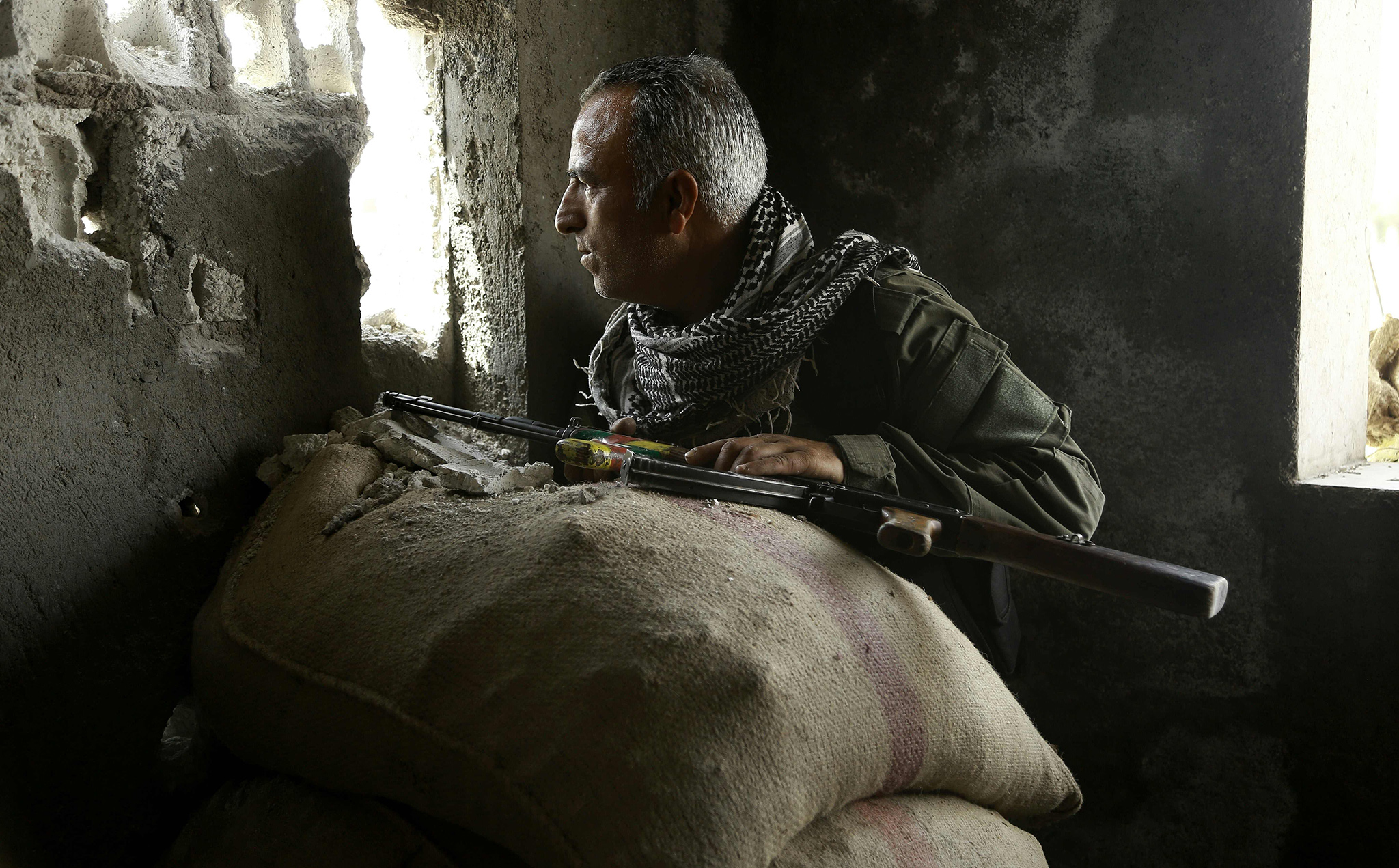 A member of the Kurdish police known as the Asayesh, observes enemy positions from a lookout point in the northeastern Syrian city of Hasakeh during ongoing fighting with regime forces on August 22, 2016. Fierce overnight clashes with regime forces allowed the Kurds to advance mostly in the south of the city, the Syrian Observatory for Human Rights said.   / AFP PHOTO / DELIL SOULEIMANDELIL SOULEIMAN/AFP/Getty Images