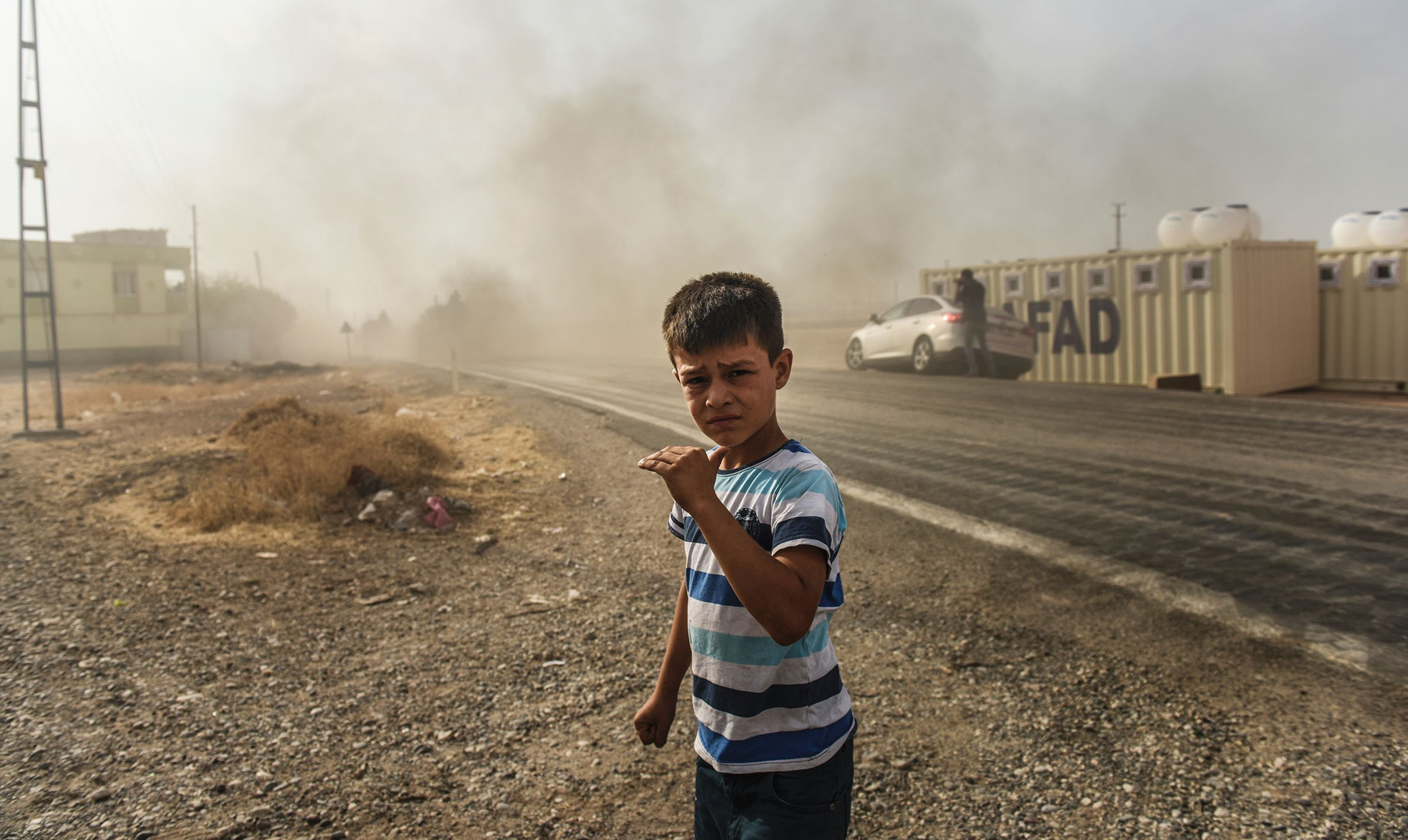This picture taken around 5 kilometres west from the Turkish Syrian border city of Karkamis in the southern region of Gaziantep, on August 25, 2016 shows a boy looking on as Turkish Army tanks drive to the Syrian Turkish border town of Jarabulus. Turkey's army backed by international coalition air strikes launched an operation involving fighter jets and elite ground troops to drive Islamic State jihadists out of a key Syrian border town. The air and ground operation, the most ambitious launched by Turkey in the Syria conflict, is aimed at clearing jihadists from the town of Jarabulus, which lies directly opposite the Turkish town of Karkamis. / AFP PHOTO / BULENT KILICBULENT KILIC/AFP/Getty Images