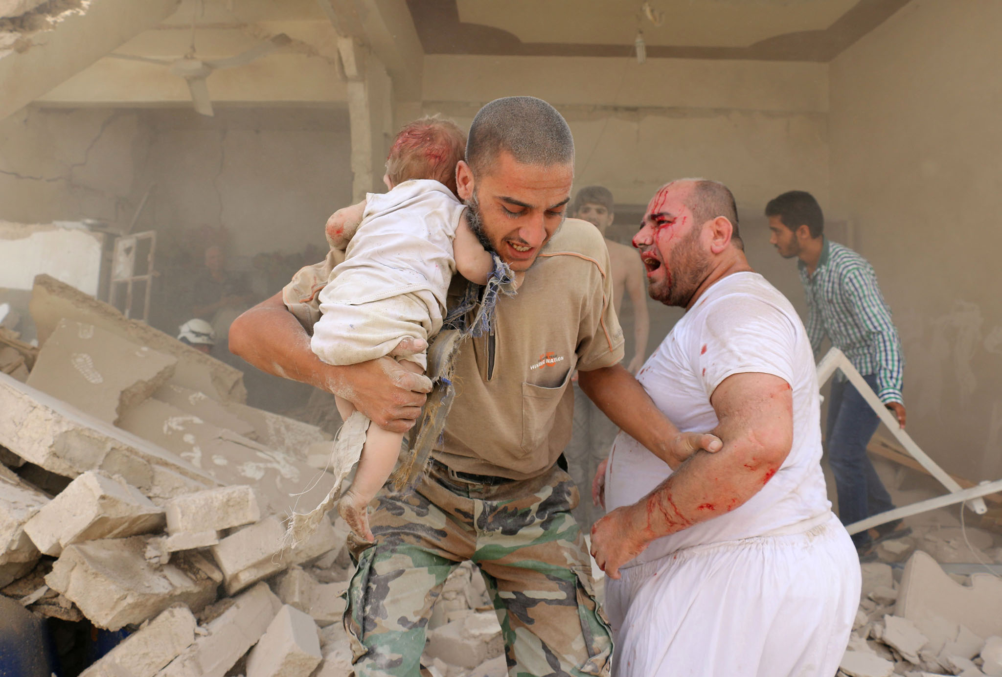 A Syrian man carries a wounded child following a barrel bomb attack on the Bab al-Nairab neighbourhood of the northern Syrian city of Aleppo
