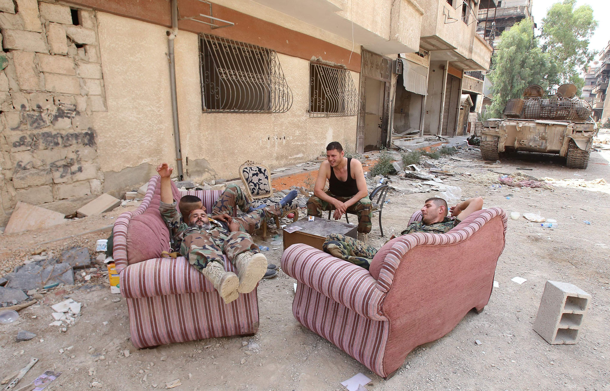 Syrian army soldiers rest in a street in the government-controlled part of the besieged town of Daraya on August 26, 2016, as thousands of rebel fighters and civilians prepared to evacuate under an accord struck a day earlier.  An estimated 8,000 people remain in the town, despite a government siege lasting four years and regular regime bombardment.    / AFP PHOTO / Youssef KARWASHANYOUSSEF KARWASHAN/AFP/Getty Images