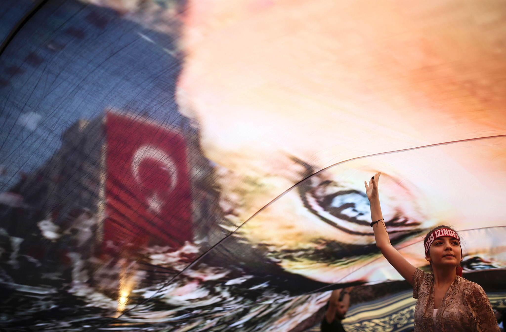A Turkish girl gestures under a huge picture of modern Turkey's founder Mustafa Kemal Ataturk at a rally in Gundogdu Square in Izmir on August 4, 2016, protesting against the failed July 15 military coup attempt, with the participation of Republican People's Party (CHP) leader Kemal Kilicdaroglu (not pictured).  Turkey issued an arrest warrant on August 4 for US-based preacher Fethullah Gulen, accusing him of ordering the coup attempt aimed at ousting President Recep Tayyip Erdogan. An Istanbul court issued the warrant, the first after the failed putsch for the reclusive cleric in Pennsylvania, the Anadolu news agency said.  / AFP PHOTO / EMRE TAZEGULEMRE TAZEGUL/AFP/Getty Images
