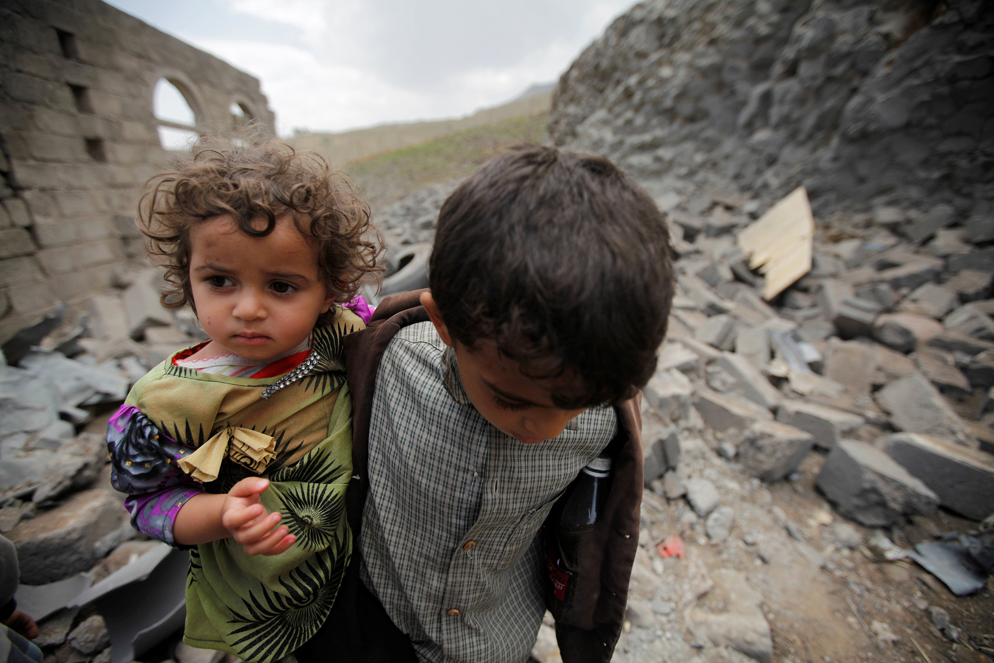 A boy carries his sister, as he walks on rubble of a houseafter it was destroyed by a Saudi-led air strike in Yemen's capital Sanaa, August 11, 2016. REUTERS/Mohamed al-Sayaghi
