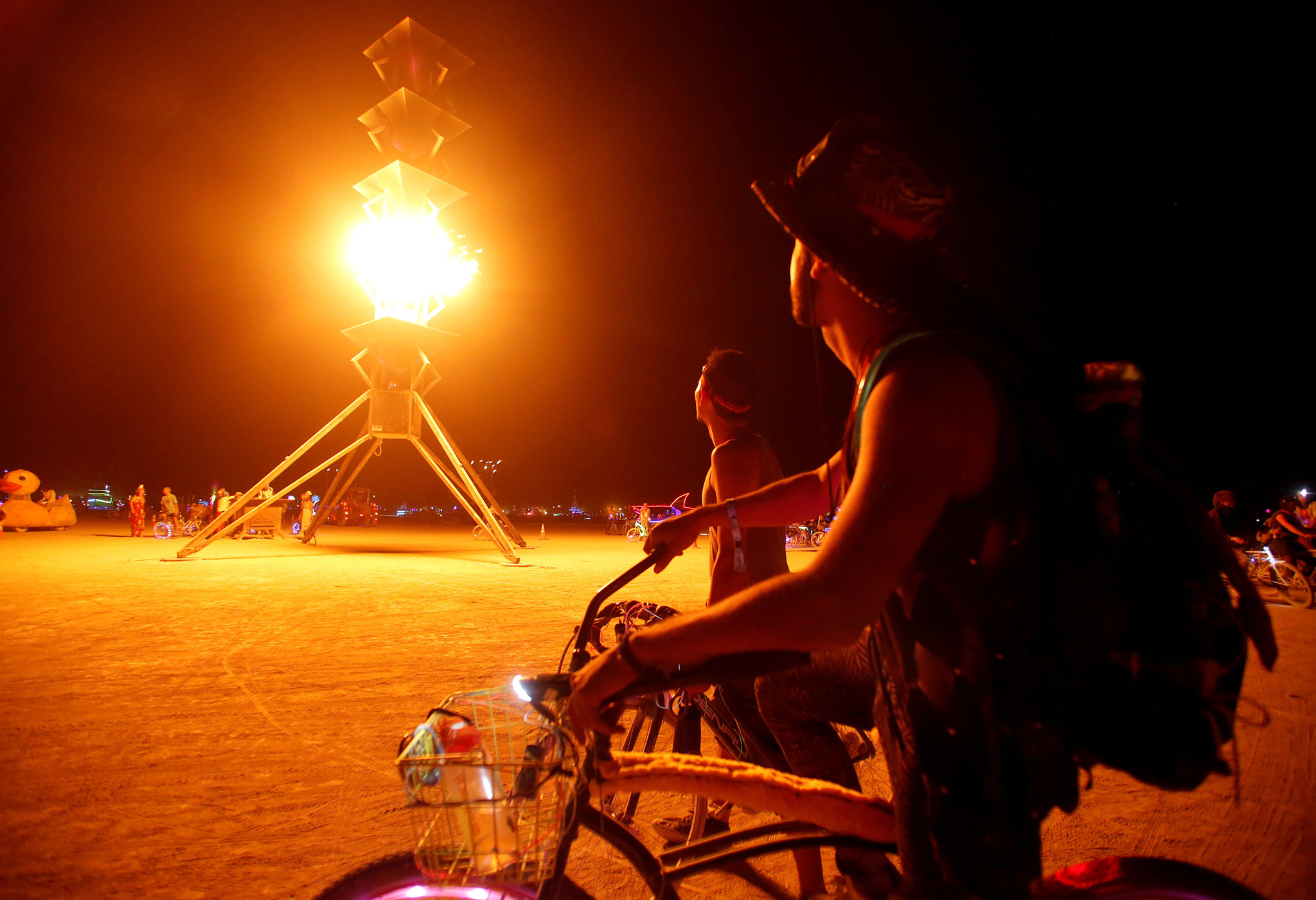 Participants watch the flames on the Spire of Fire as approximately 70,000 people from all over the world gather for the 30th annual Burning Man arts and music festival in the Black Rock Desert of Nevada