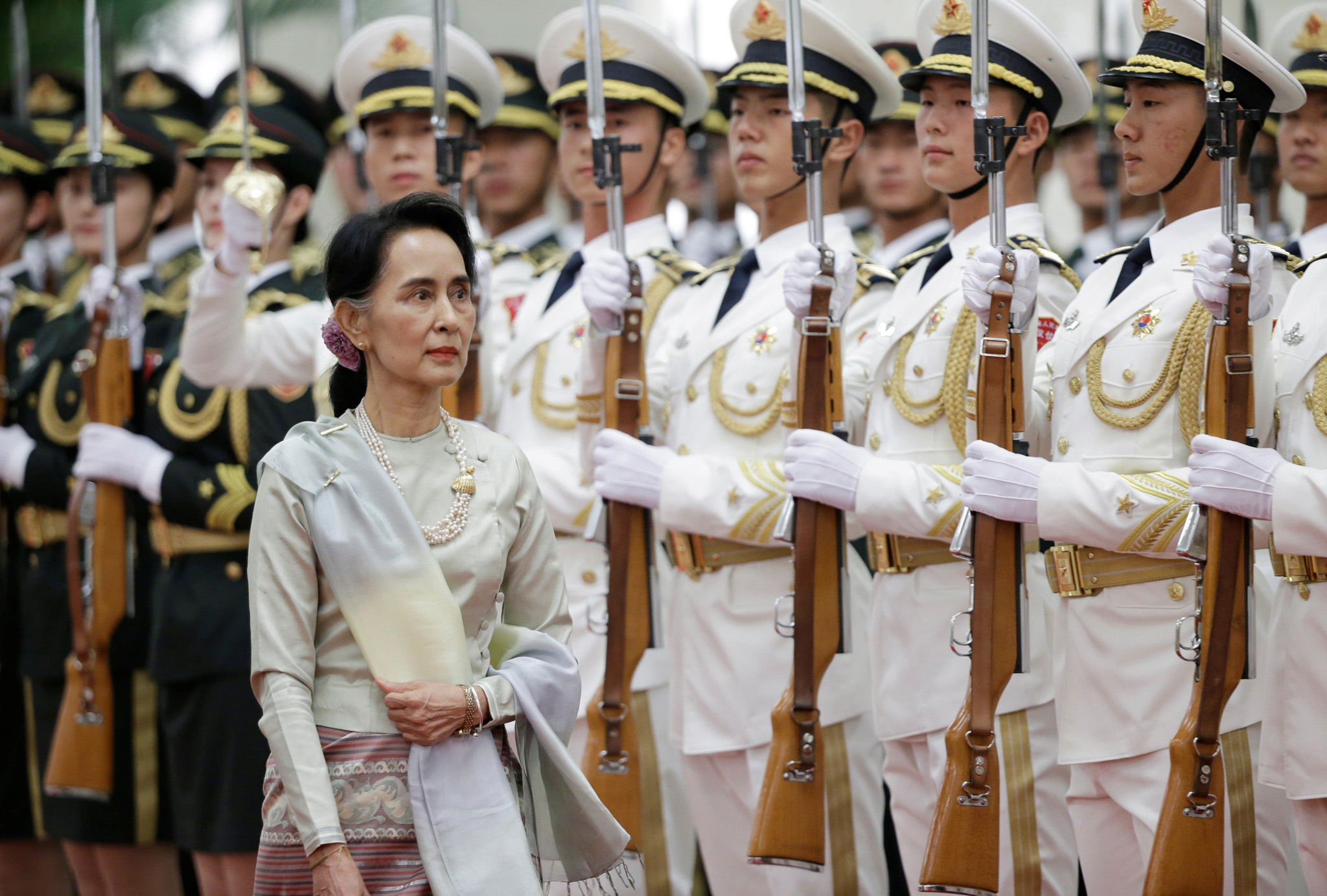 Myanmar State Counselor Aung San Suu Kyi reviews honour guards during a welcoming ceremony at the Great Hall of the People in Beijing