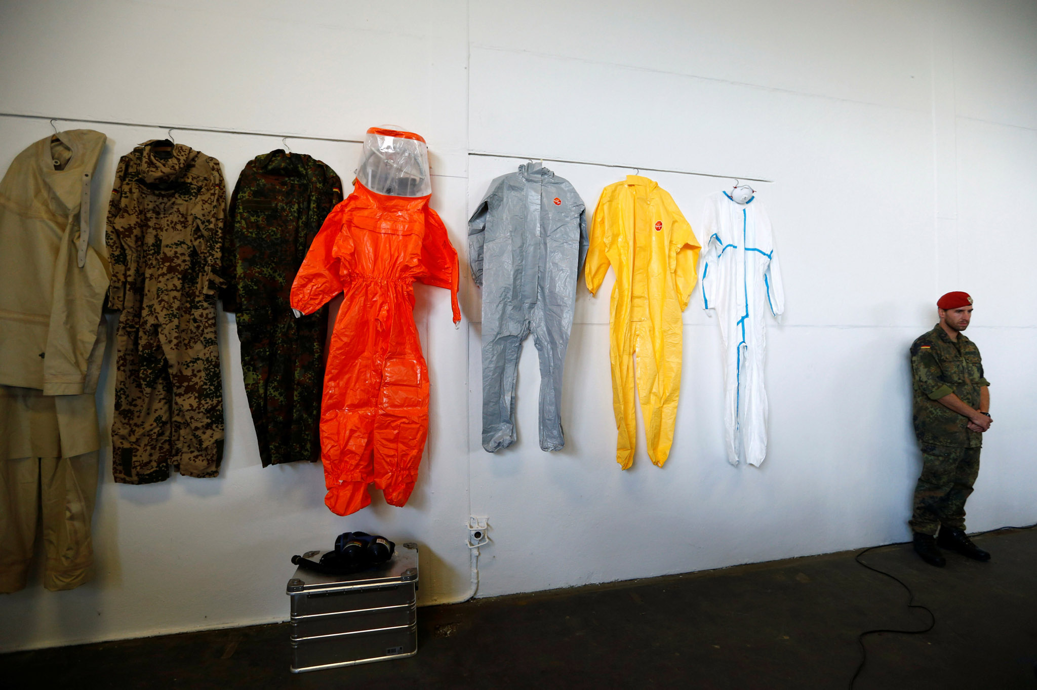 A soldier stands next to various overalls at the Bundeswehr ABC defence battalion 750 in Bruchsal, Germany
