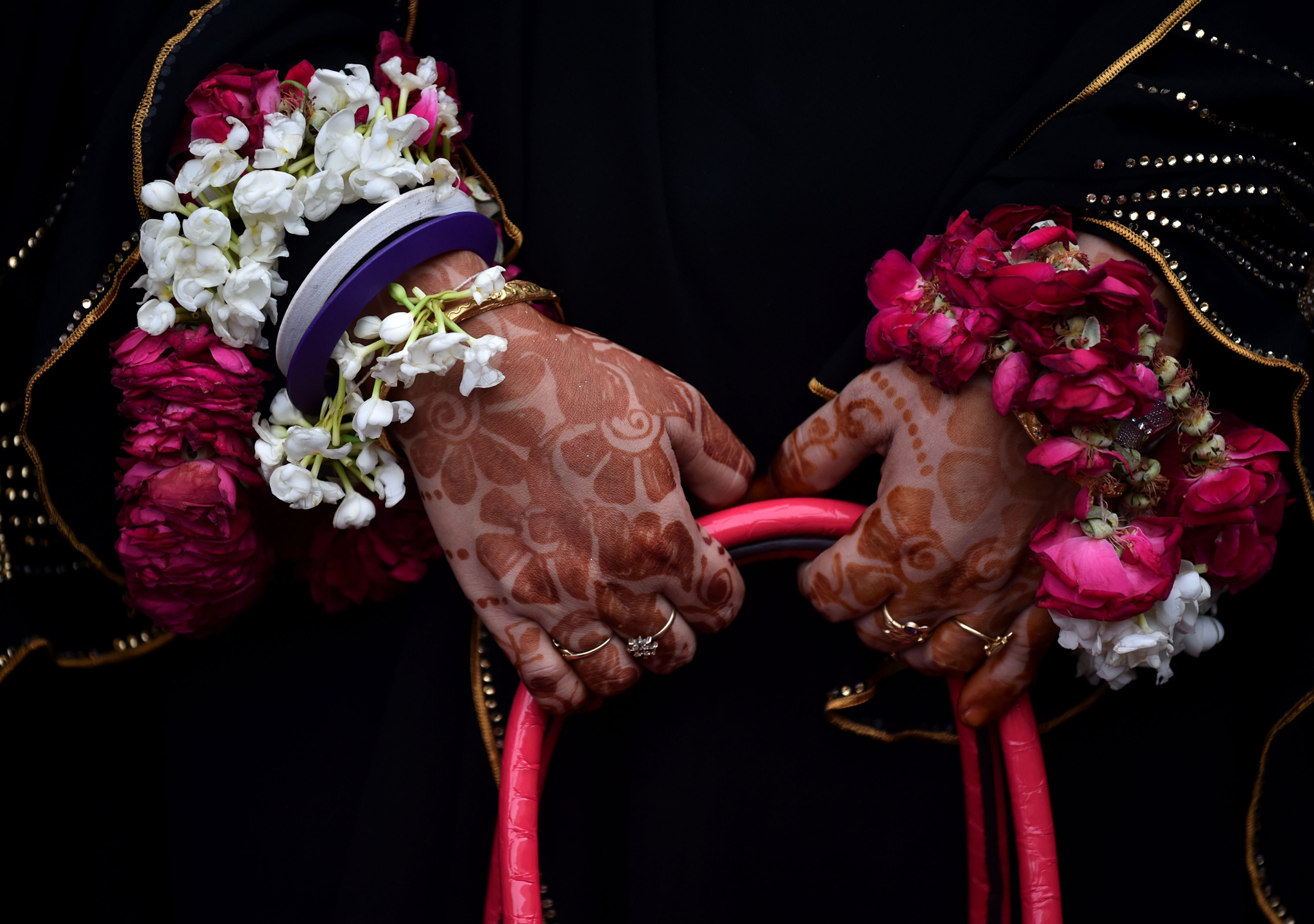 An Indian Muslim pilgrim whose hands are decorated with henna and garlands is phhotographed before leaving for the annual Hajj pilgrimage