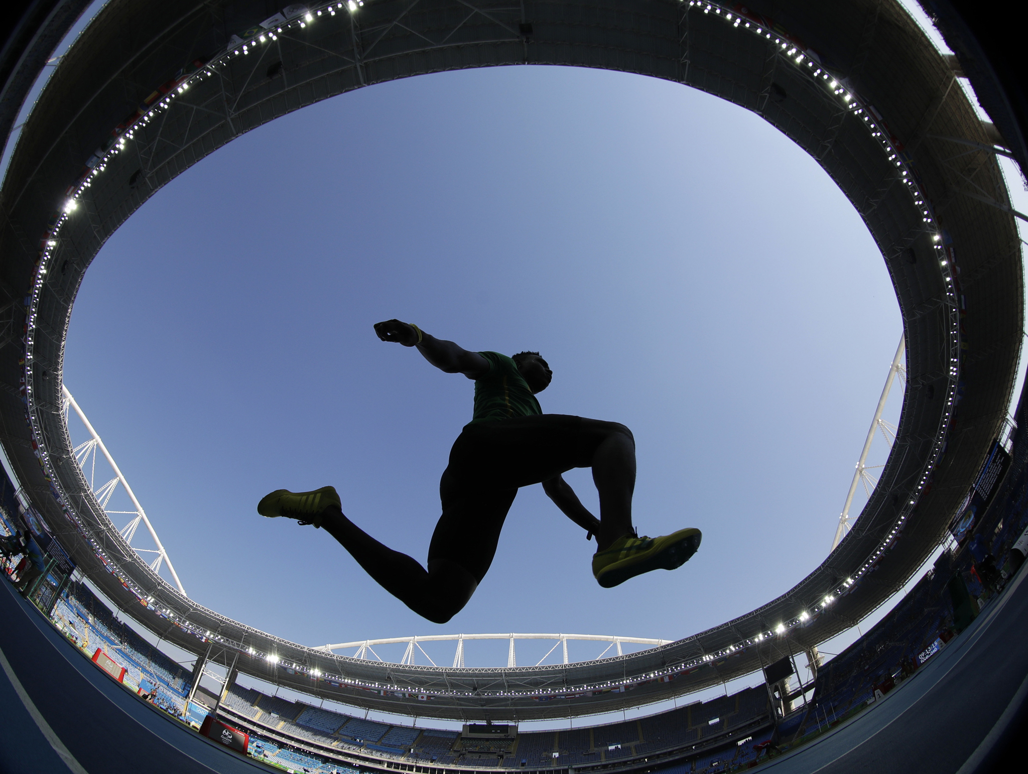 An unidentified athlete makes an attempt in the men's triple jump qualification during the athletics competitions in the Olympic stadium