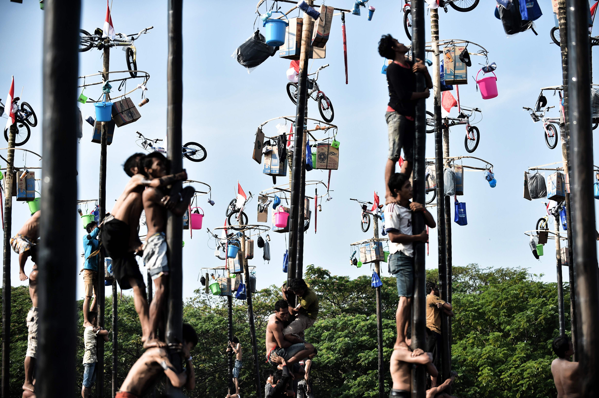 Participants struggle to reach the prizes on the top of greasy slippery poles in Jakarta on August 17, 2016, as part of Indonesia's celebrations to mark its 71st independent day anniversary.