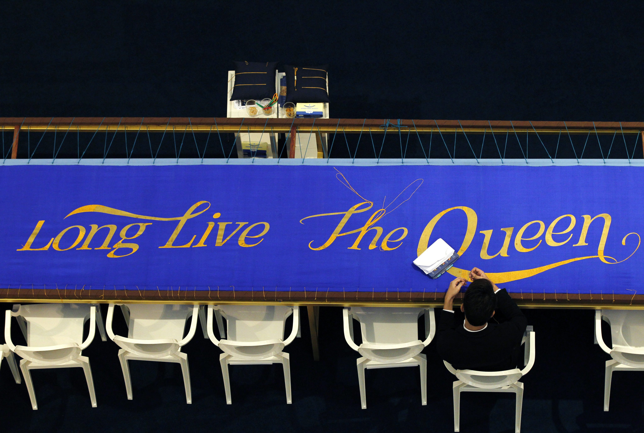 A Thai well-wisher embroiders with golden thread on a seven meter long silk banner reading 'Long Live the Queen' as part of Thai Queen Sirikit's birthday preparations in Bangkok, Thailand