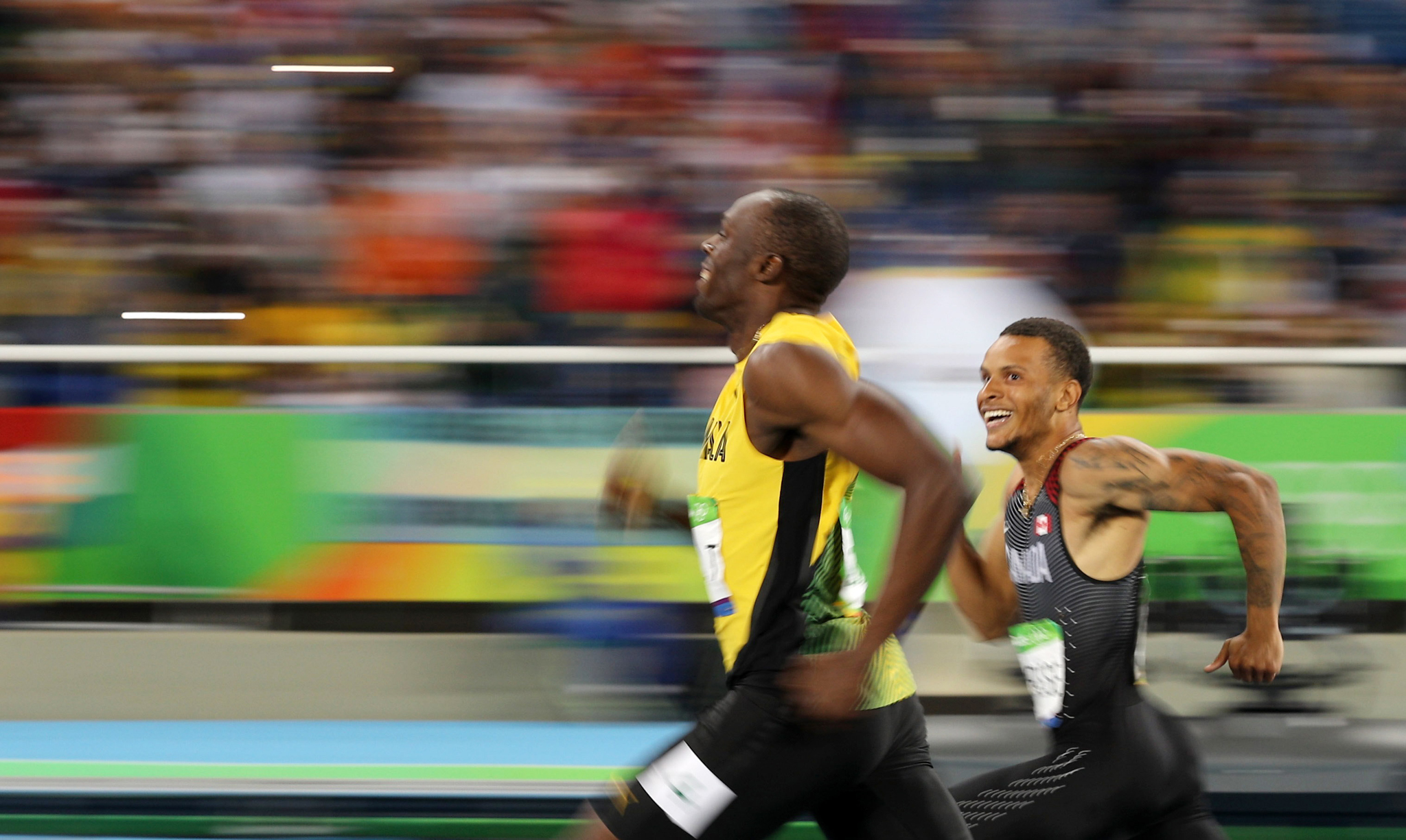 Athletics - Semifinal - Men's 200m Semifinals - Olympic Stadium - Rio de Janeiro, Brazil - 17/08/2016. Usain Bolt (JAM) of Jamaica and Andre De Grasse (CAN) of Canada smile as they compete