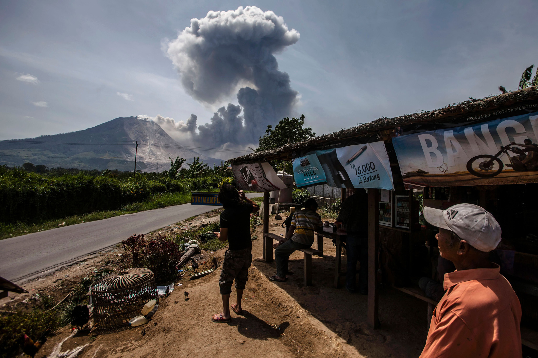 Indonesian residents look at the Mount Sinabung volcano as it spews volcanic ash near the Tiga Pancur village in Karo, North Sumatra