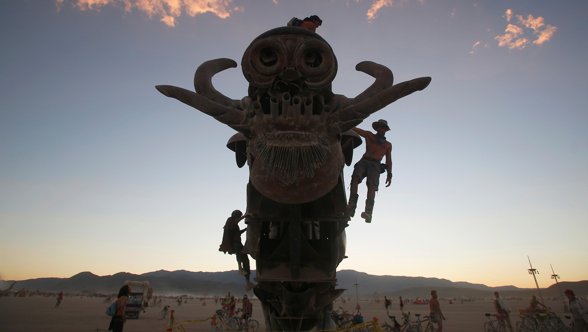 Participants climb on an art installation as approximately 70,000 people from all over the world gather for the 30th annual Burning Man arts and music festival in the Black Rock Desert of Nevada, U.S.