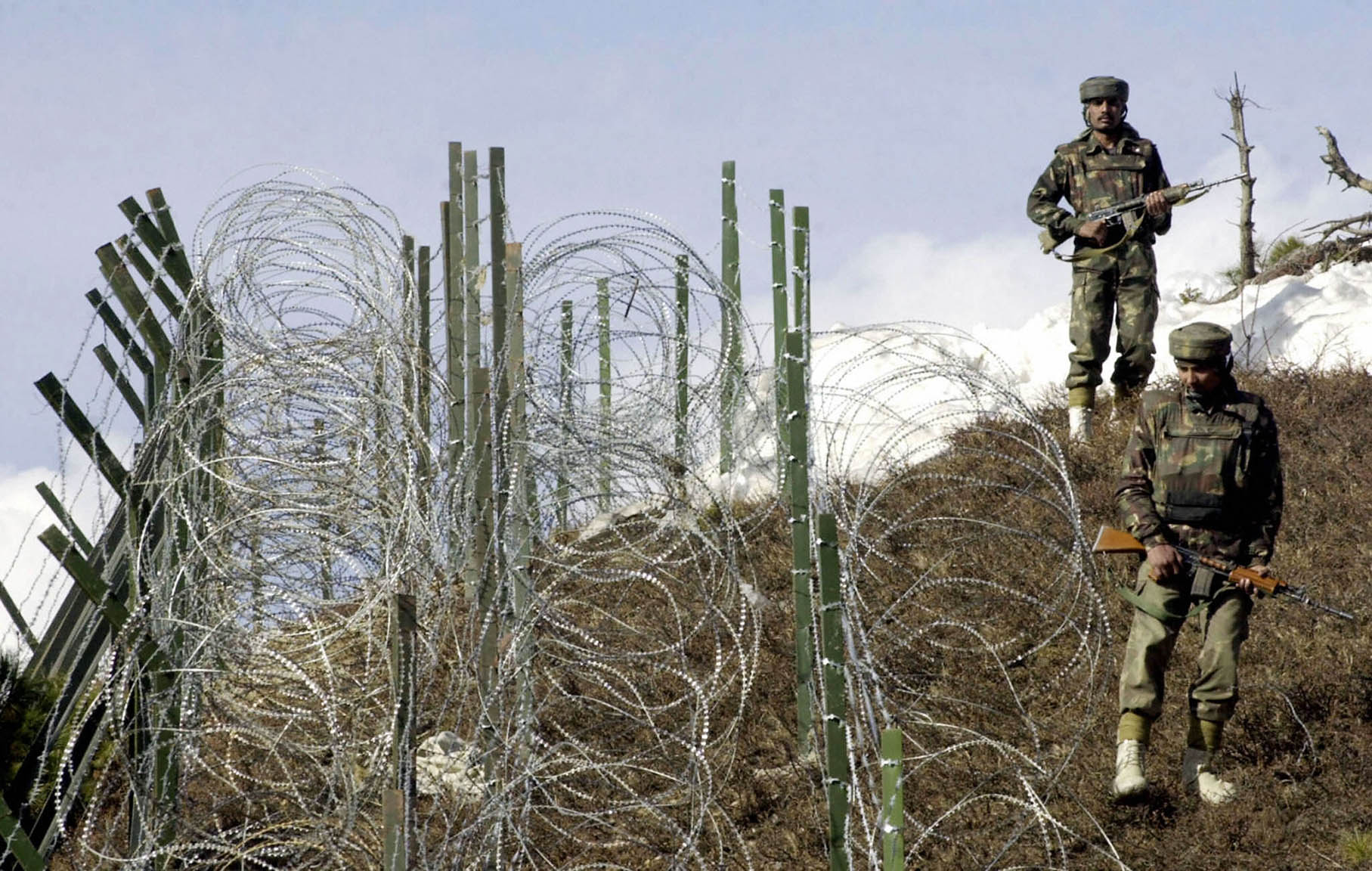 Indian soldiers as they patrol along a barbed-wire fence near Baras Post