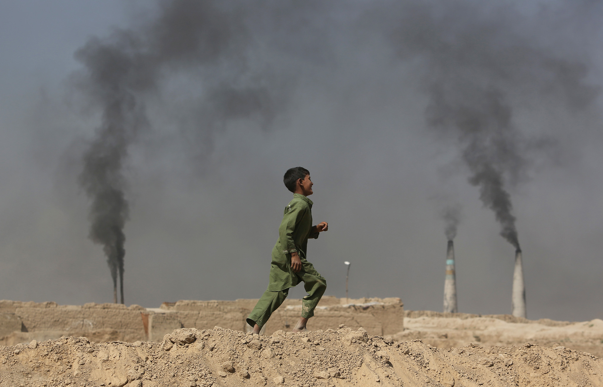 An Afghan boy runs past at a local brick factory on the outskirts of Kabul, Afghanistan, Monday, Sept. 19, 2016. (AP Photo/Rahmat Gul)