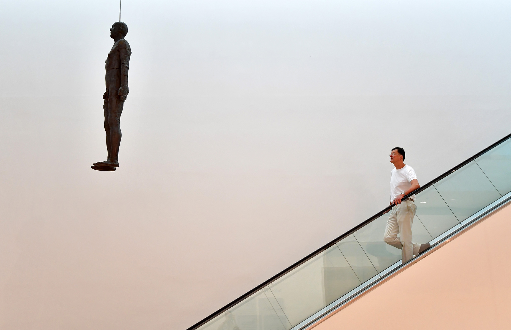 British artist Anthony Gormley poses for a photograph next to his artwork entitled 'Object, 199', a life-size cast-iron sculpture cast from the artist's body and hung from the ceiling of the National Portrait Gallery, during a press preview on September 7, 2016 in London, England. The work is accompanied on October 5 by 'Fall, 1999', a selection of drawings also by Mr Gormley.  (Photo by Carl Court/Getty Images)