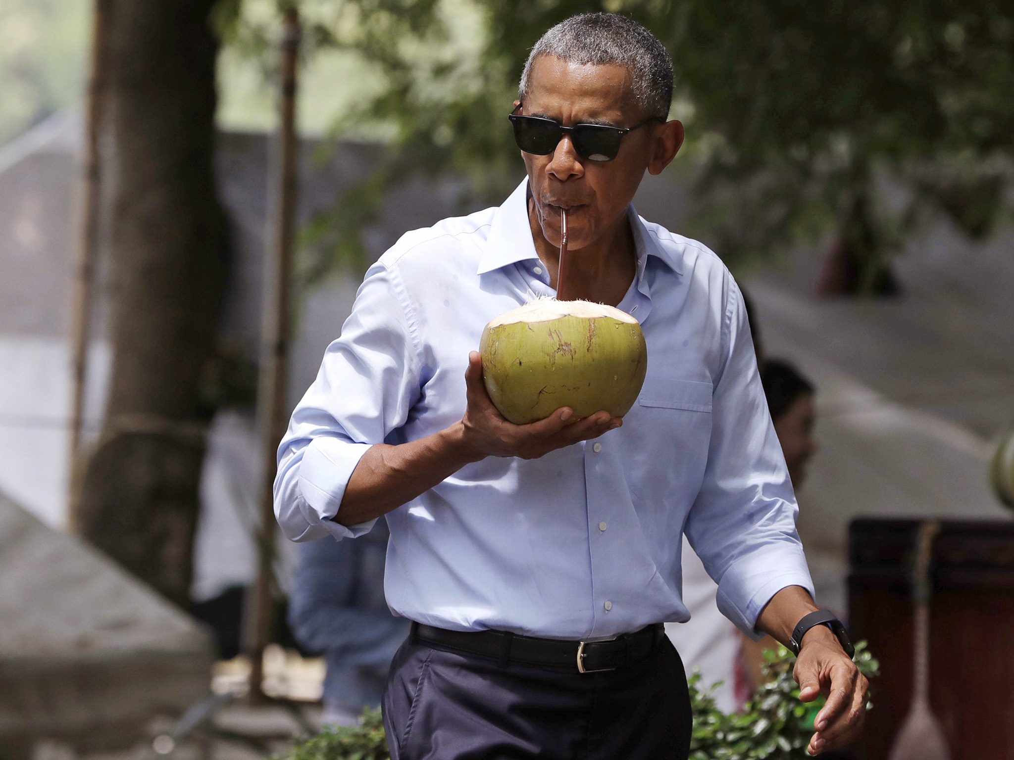 U.S. President Barack Obama drinks from a fresh coconut along the banks of the Mekong River in the Luang Prabang, Laos