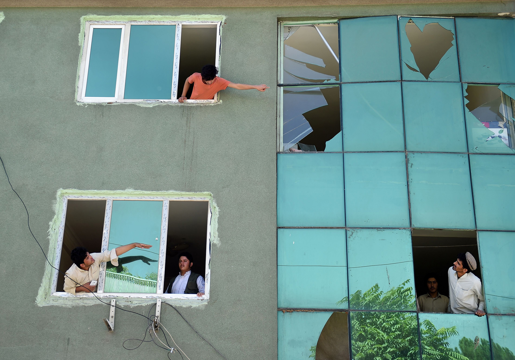 Afghan residents look out from broken windows of a building near the site of an attack following a car bomb blast that targeted the CARE International compound at Shar-e-Naw in Kabul