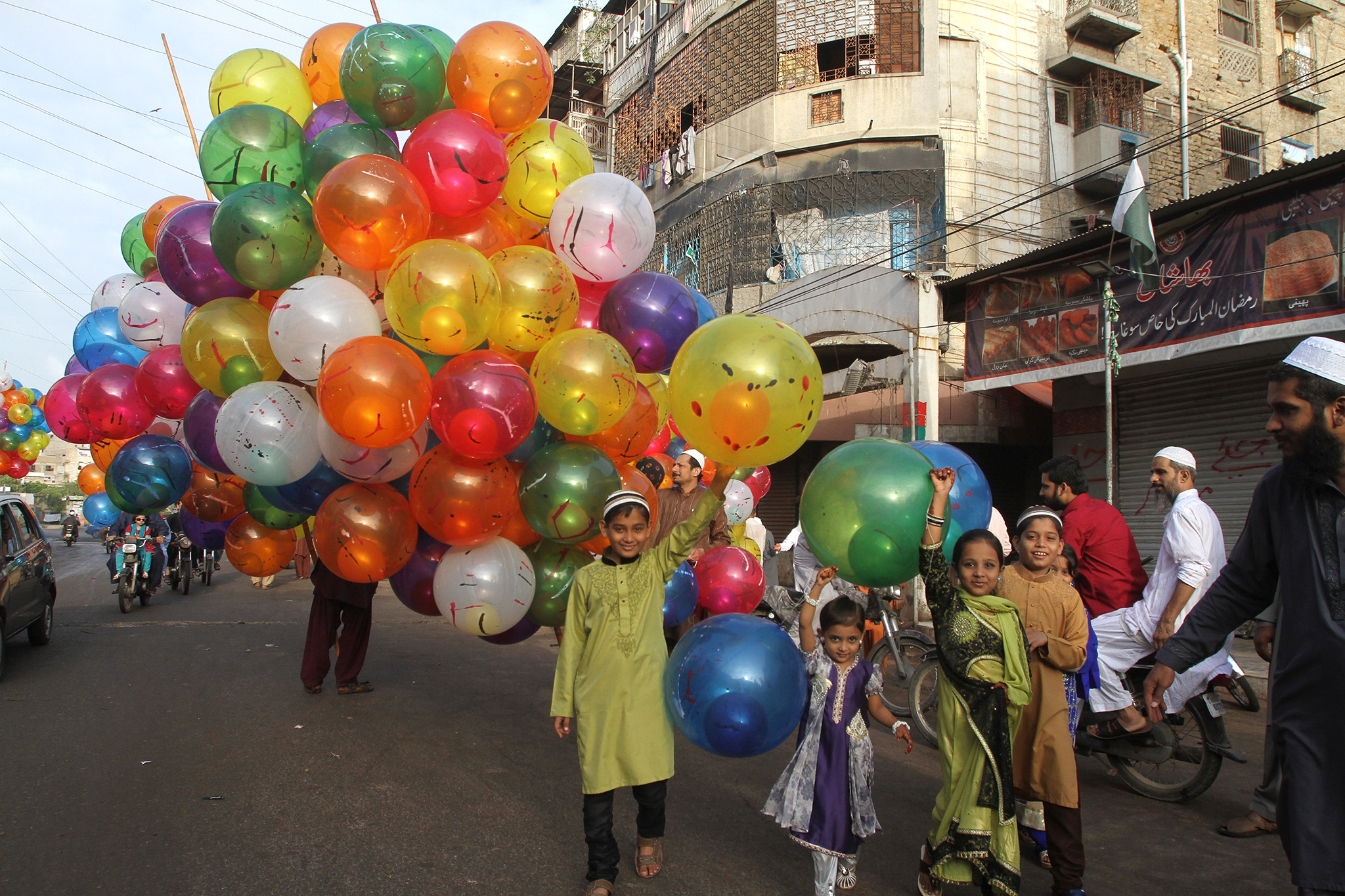 Pakistani children buy balloons to celebrate the Eid al Adha in Karachi, Pakistan, Tuesday, Sept. 13, 2016. Pakistani Muslims are celebrating the Eid al-Adha, or the Feast of the Sacrifice, on Tuesday to mark the willingness of the Prophet Ibrahim -- Abraham to Christians and Jews -- to sacrifice his son. During the holiday Muslims slaughter sheep and cattle, distribute part of the meat to the poor and eat the rest. (AP Photo/Fareed Khan)