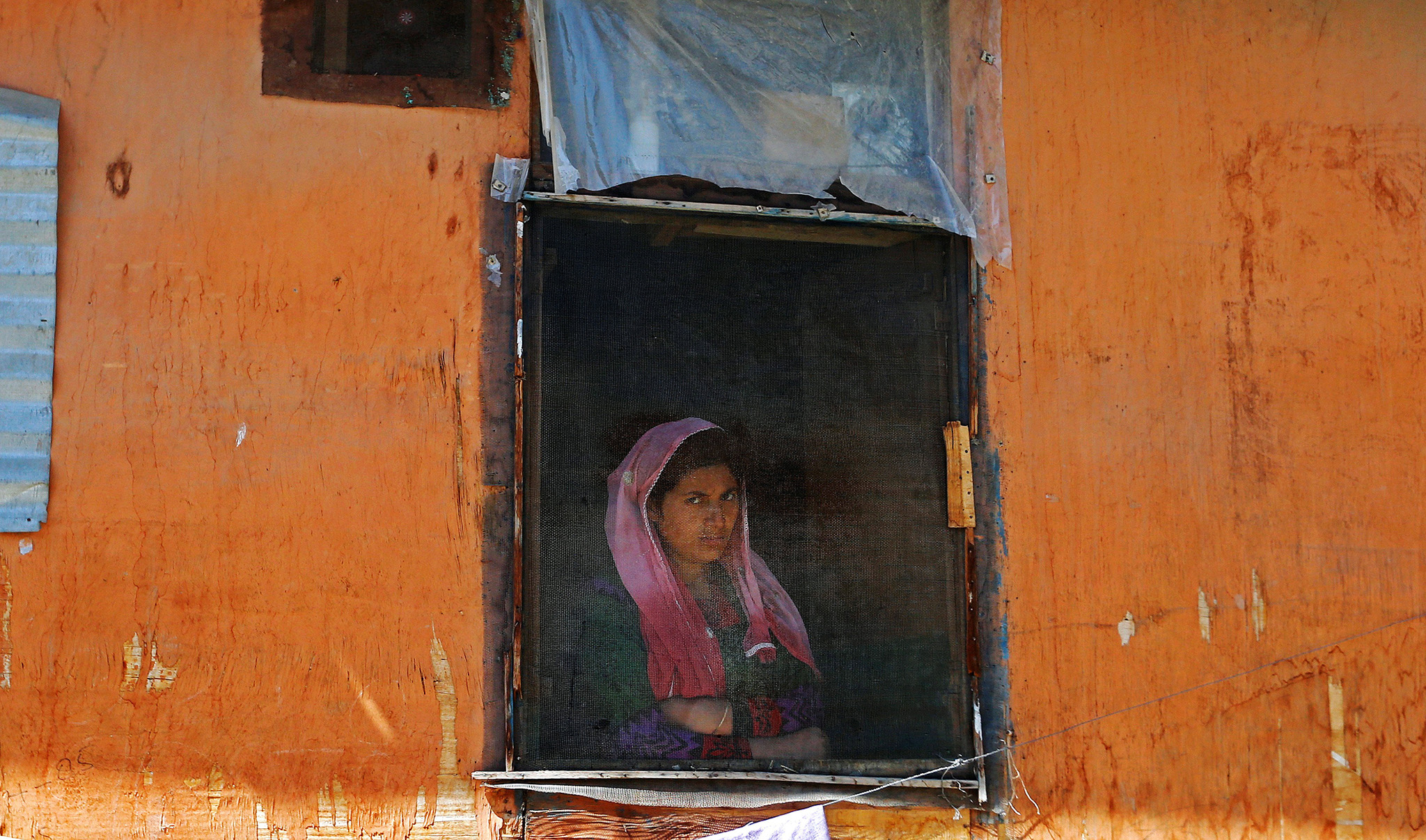 A woman looks out from a window in Srinagar,during a protest against the recent killings in Kashmir