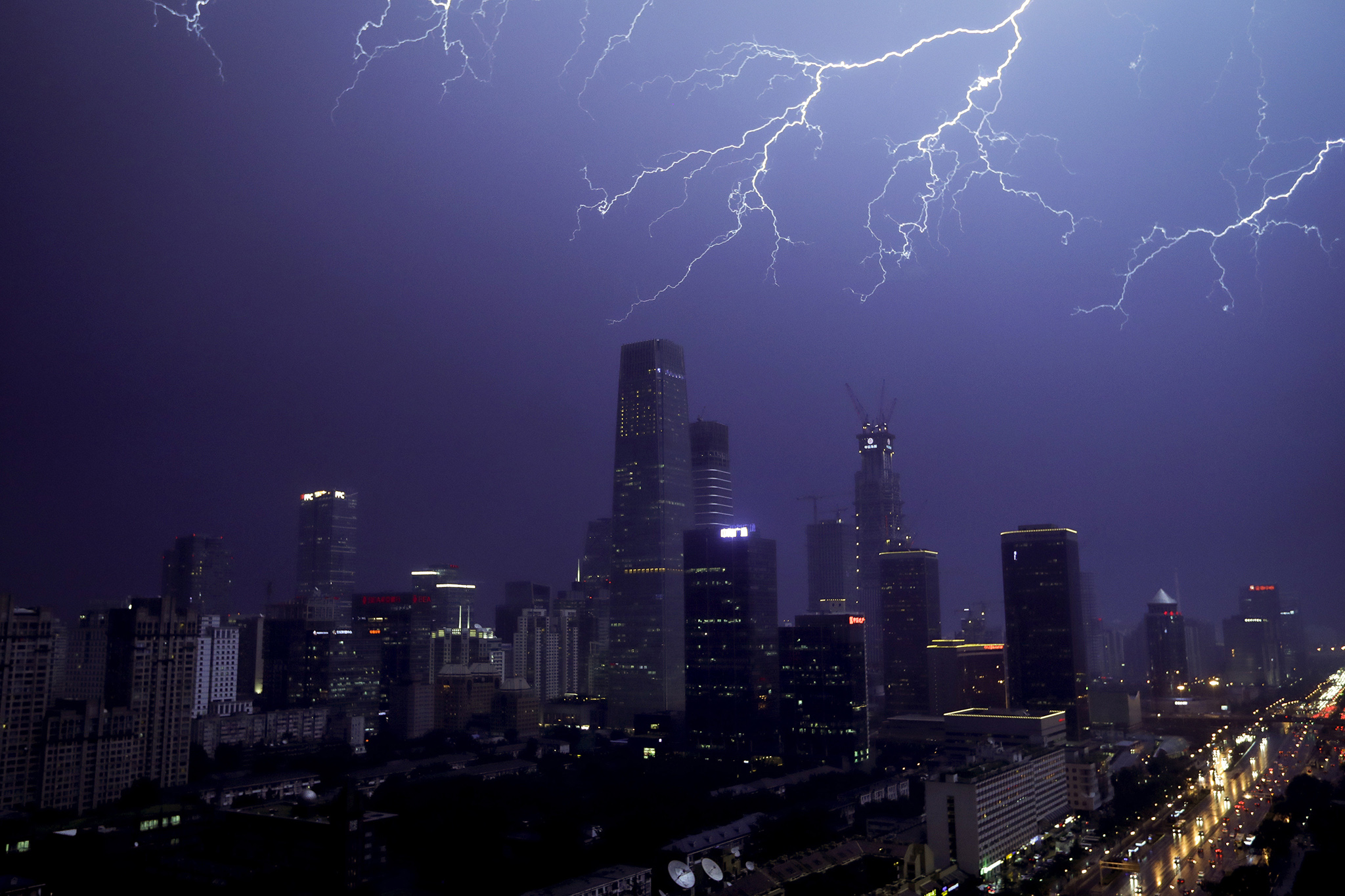 Lightning flashes above skyscrapers in Central Business District during a rainstorm in Beijing, Wednesday