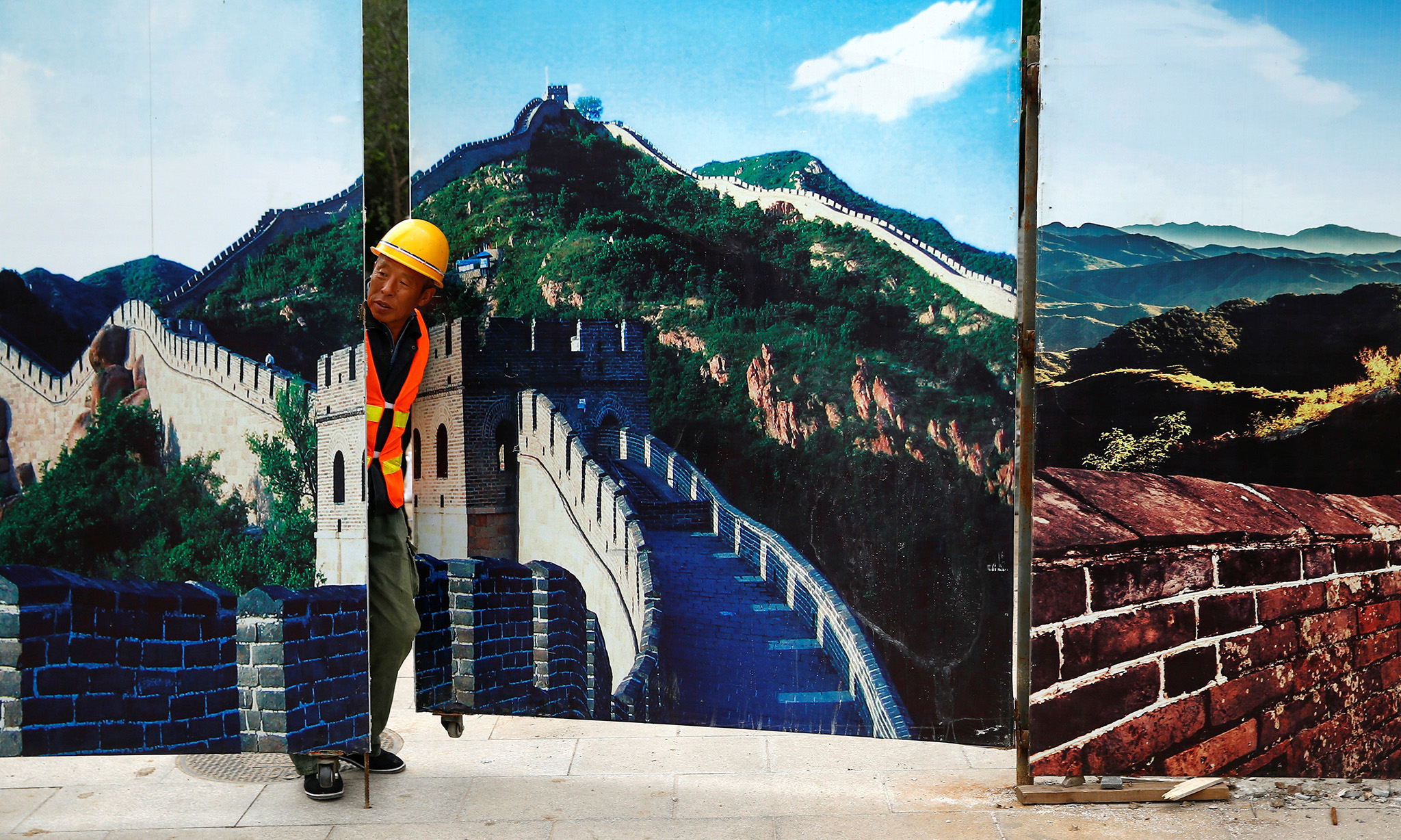 A worker looks through the fence of a construction site that is decorated with pictures of the Great Wall at Badaling, north of Beijing, China, September