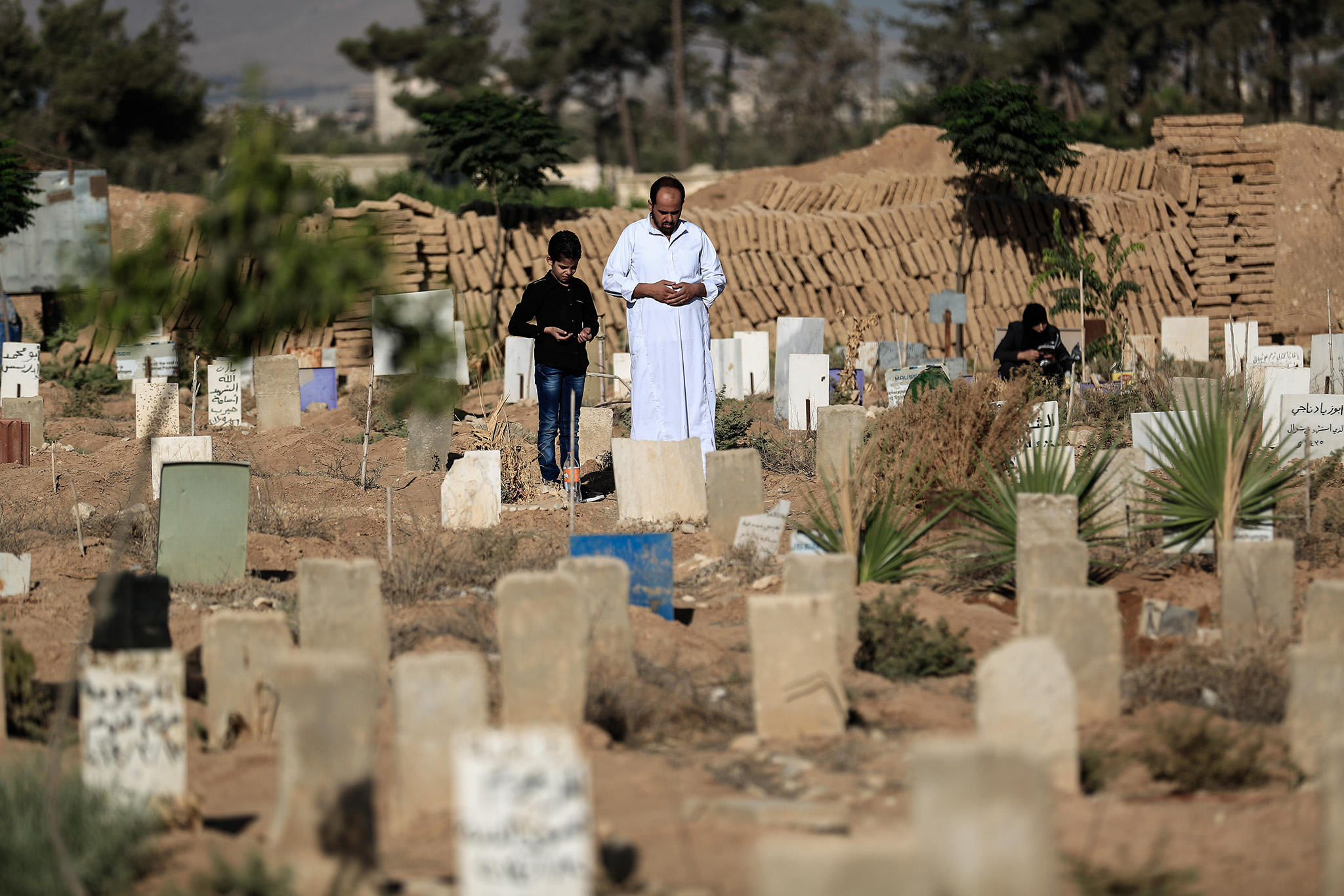 A Syrian man and his son pray over the grave of a relative at a cemetery in the rebel-held town of Douma, east of the capital Damascus, on September 12, 2016, on the first day of the Muslim holiday of Eid al-Adha. / AFP PHOTO / Sameer Al-DoumySAMEER AL-DOUMY/AFP/Getty Images