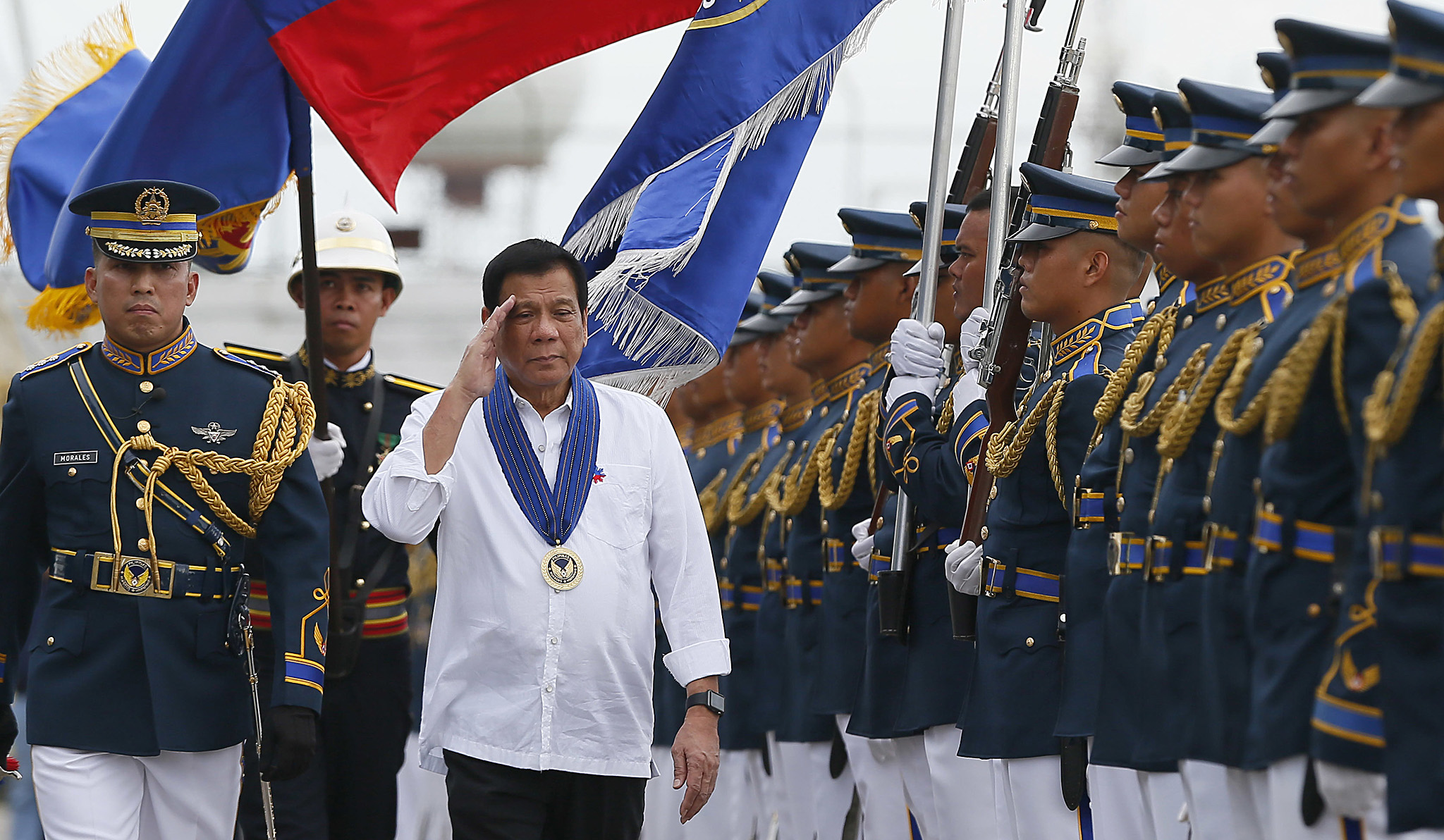 "Philippine President Rodrigo Duterte salutes as he reviews the troops during his ""Talk with the Airmen"" on the anniversary of the 250th Presidential Airlift Wing Tuesday, Sept. 13, 2016 at the Philippine Air Force headquarters in suburban Pasay city, southeast of Manila, Philippines. On Monday, President Duterte, in his first public statement opposing the presence of American troops, said he wants U.S. forces out of his country's south and blamed America for inflaming Muslim insurgencies in the region. (AP Photo/Bullit Marquez)"