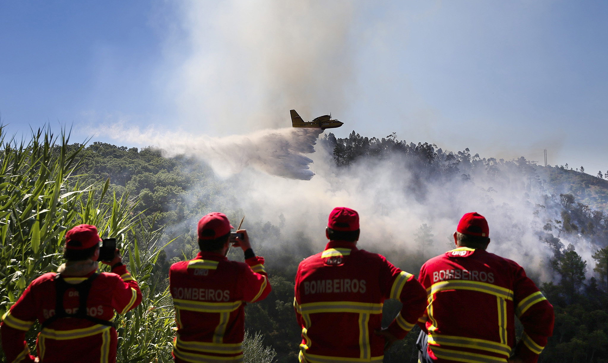 Portuguese fireman watch as a Canadair sprays water at a forest fire in the area of Serra de Monchique, in Monchique, Portugal, 09 September 2016. The Monchique fire has been burning since 03 September, forcing the evacuation of several towns.  EPA/JOSE SENA GOULAO