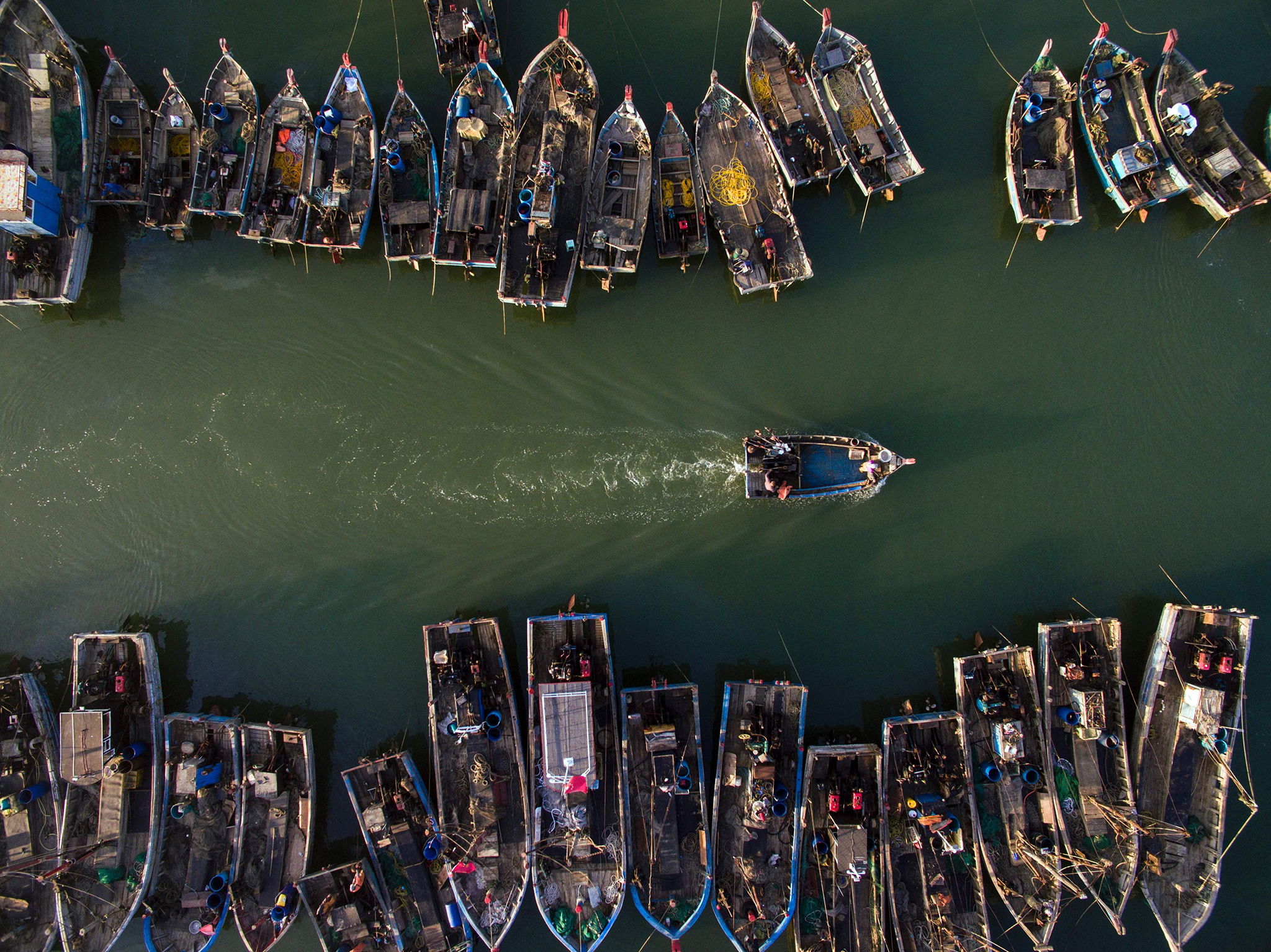 This picture taken on September 19, 2016 shows people onboard fishing boats heading out to sea in order to catch crabs, in Xianrendao in China's northeastern Liaoning province.