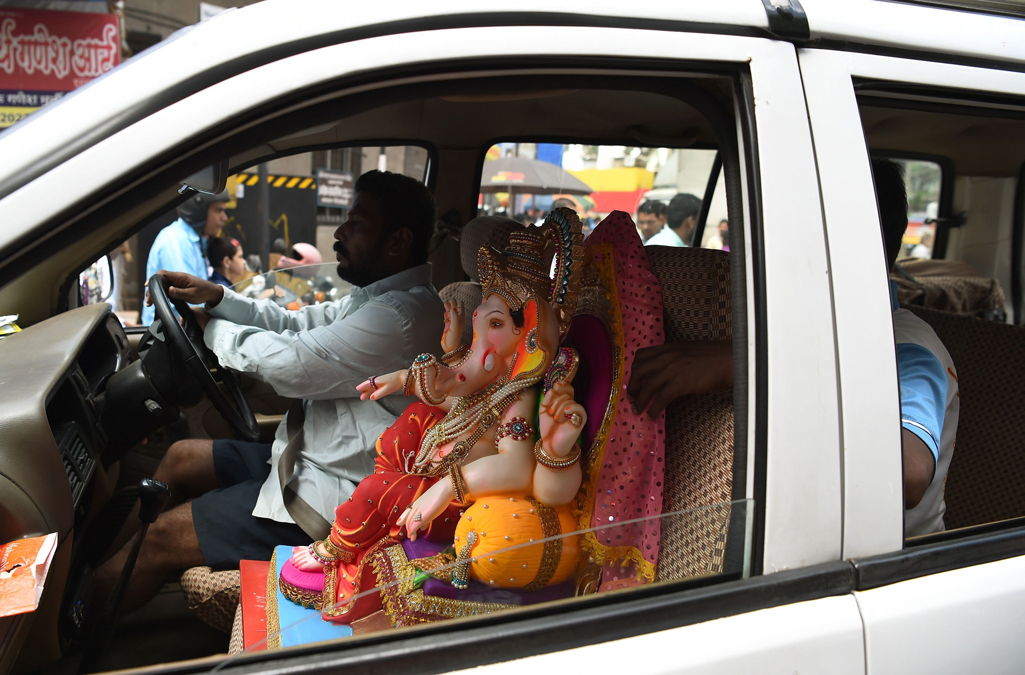 An Indian Hindu devotee transports an idol of the elephant-headed Hindu god, Lord Ganesha in his car, for Ganesh Chaturthi in Mumbai on September 5, 2015.  The Ganesh Chaturthi festival, a popular 11-day religious festival which is annually celebrated across India, runs this year from September 5-15, and culminates with the im